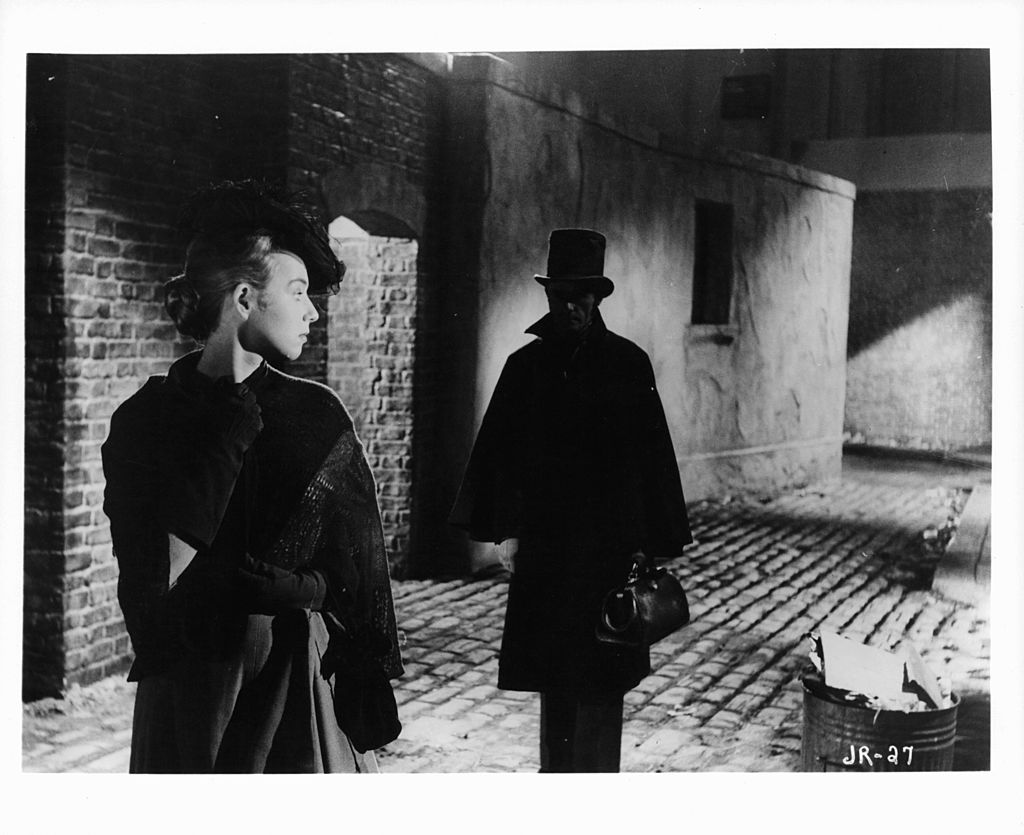 Actress looking back at a man following her in a scene from the film 'Jack The Ripper', 1959.