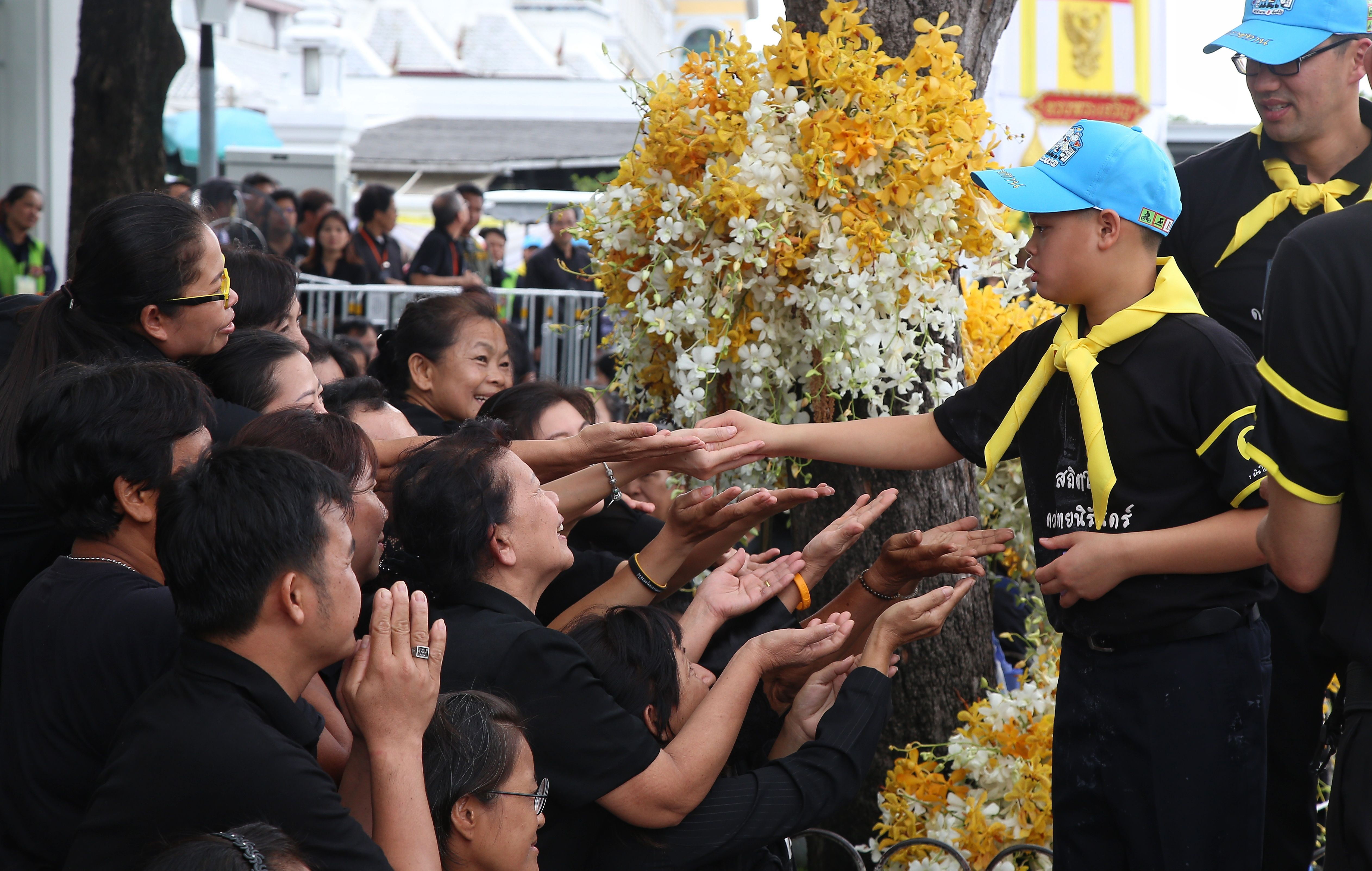 This picture by Thailand's Dailynews shows Prince Dipangkorn Rasmijoti (2nd R), 12, greeting well-wishers in Bangkok on October 25, 2017, near the site of where his grandfather, the late Thai King Bhumibol Adulyadej, will be cremated on October 26.