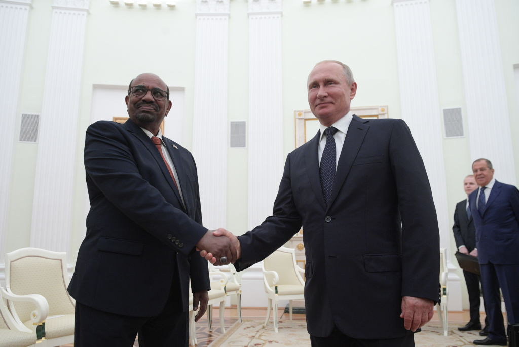 Sudan's President Omar al-Bashir (L) and Russia's President Vladimir Putin shake hands during a meeting at the Moscow Kremlin in July 2018