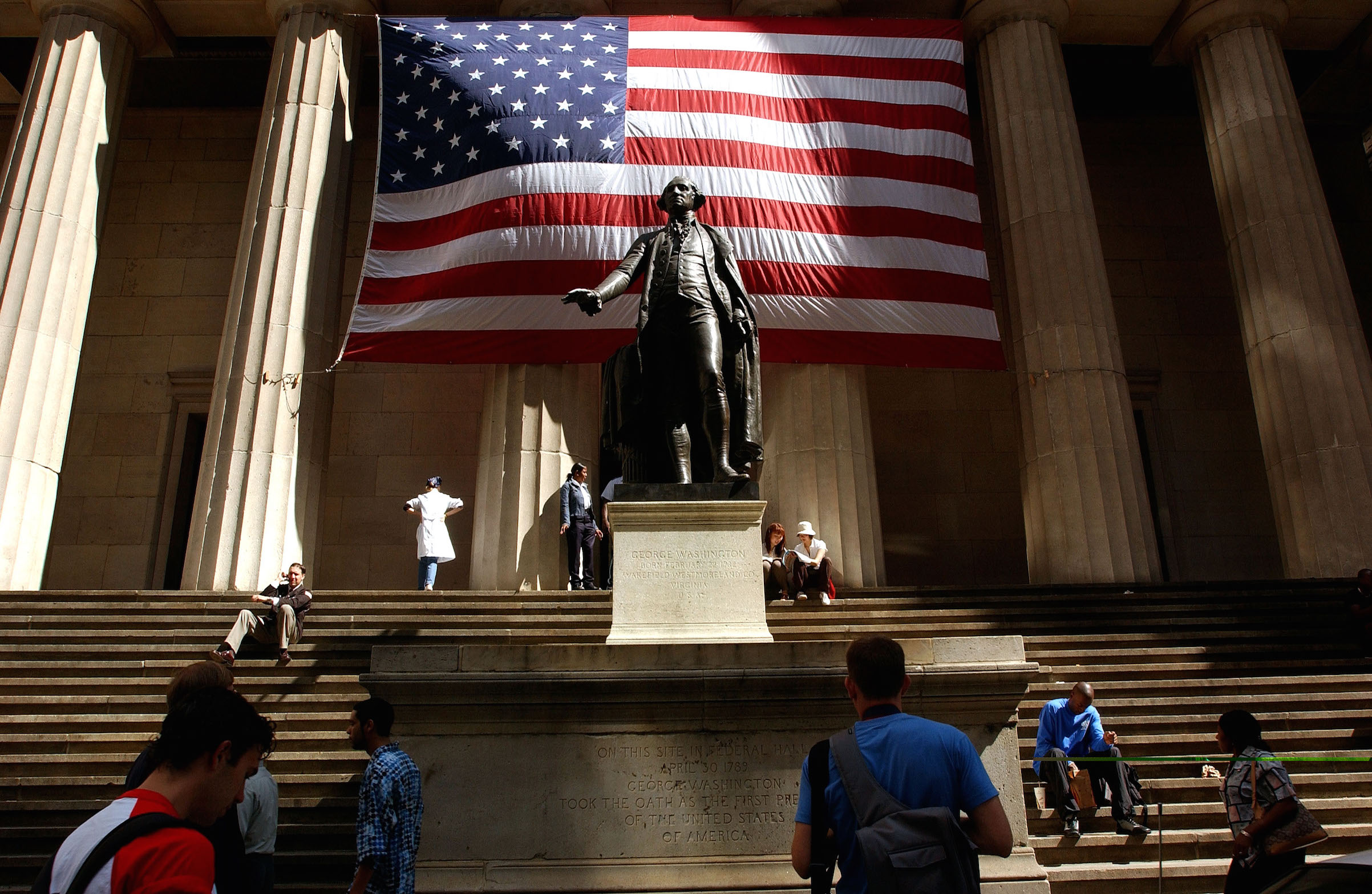 Pedestrians walk around the George Washington statue in front of Federal Hall Sept. 5, 2002 in New York City.
