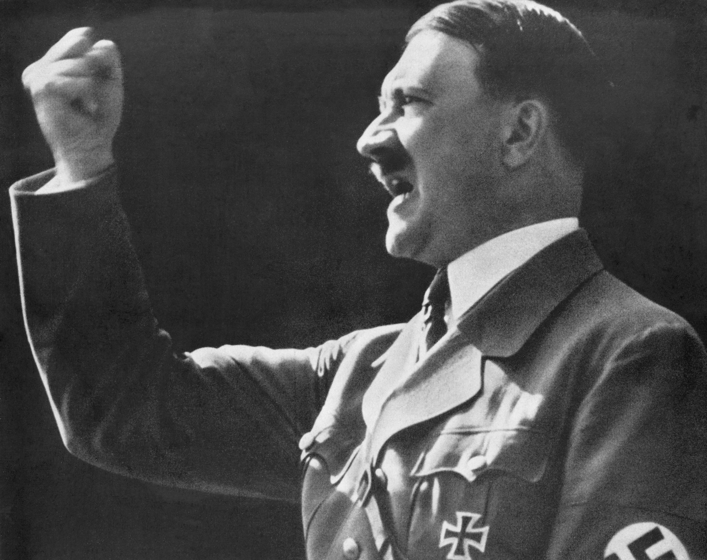 Adolf Hitler raises a defiant, clenched fist during a speech.