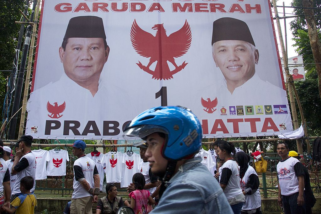 A motorcyclist rides past a large election poster for Indonesian Presidential candidate Prabowo Subianto in Jakarta, Indonesia on July 5, 2014.