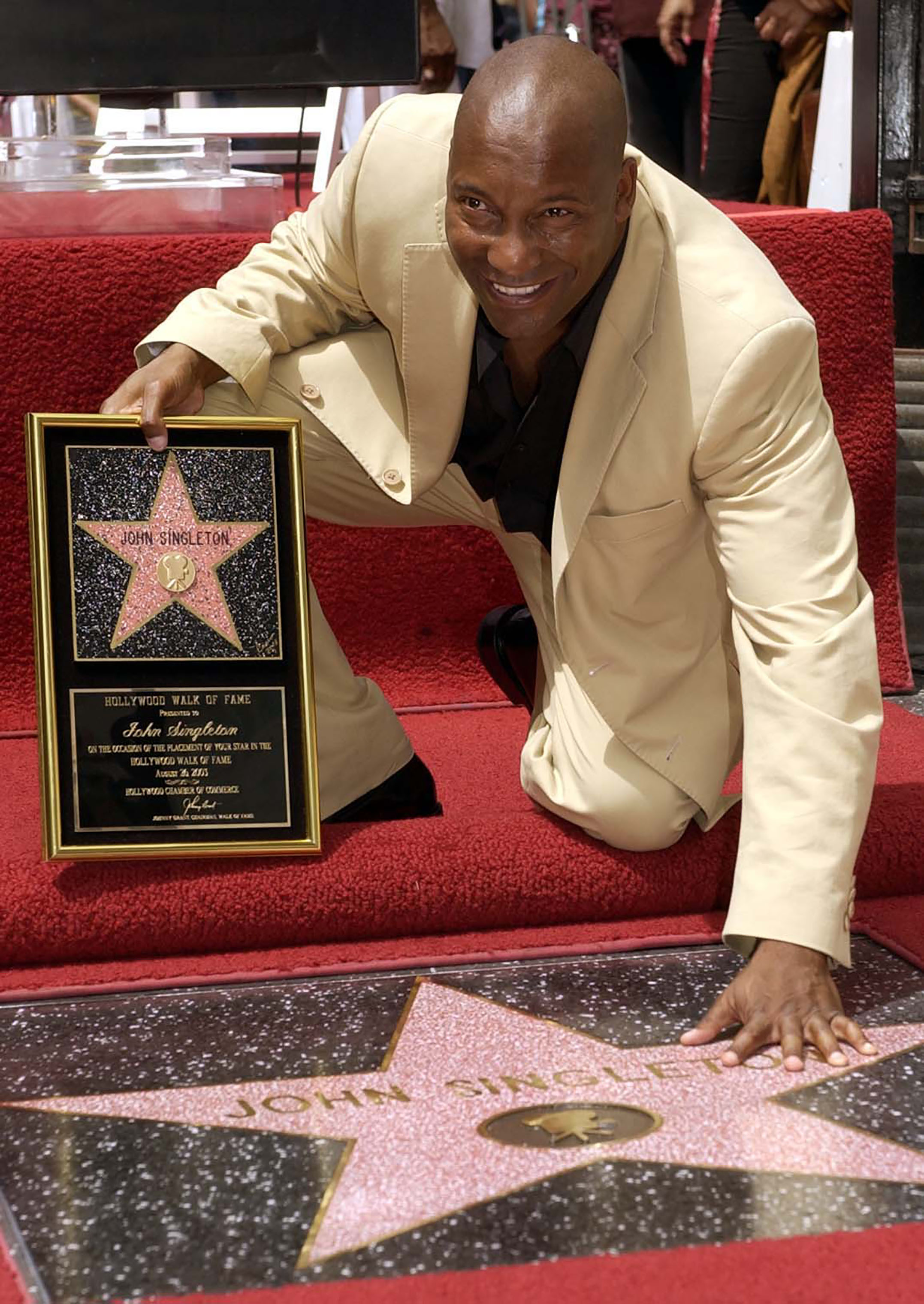 Director John Singleton touches his new star on the Hollywood Walk of Fame in Los Angeles, Tuesday, Aug. 26, 2003.