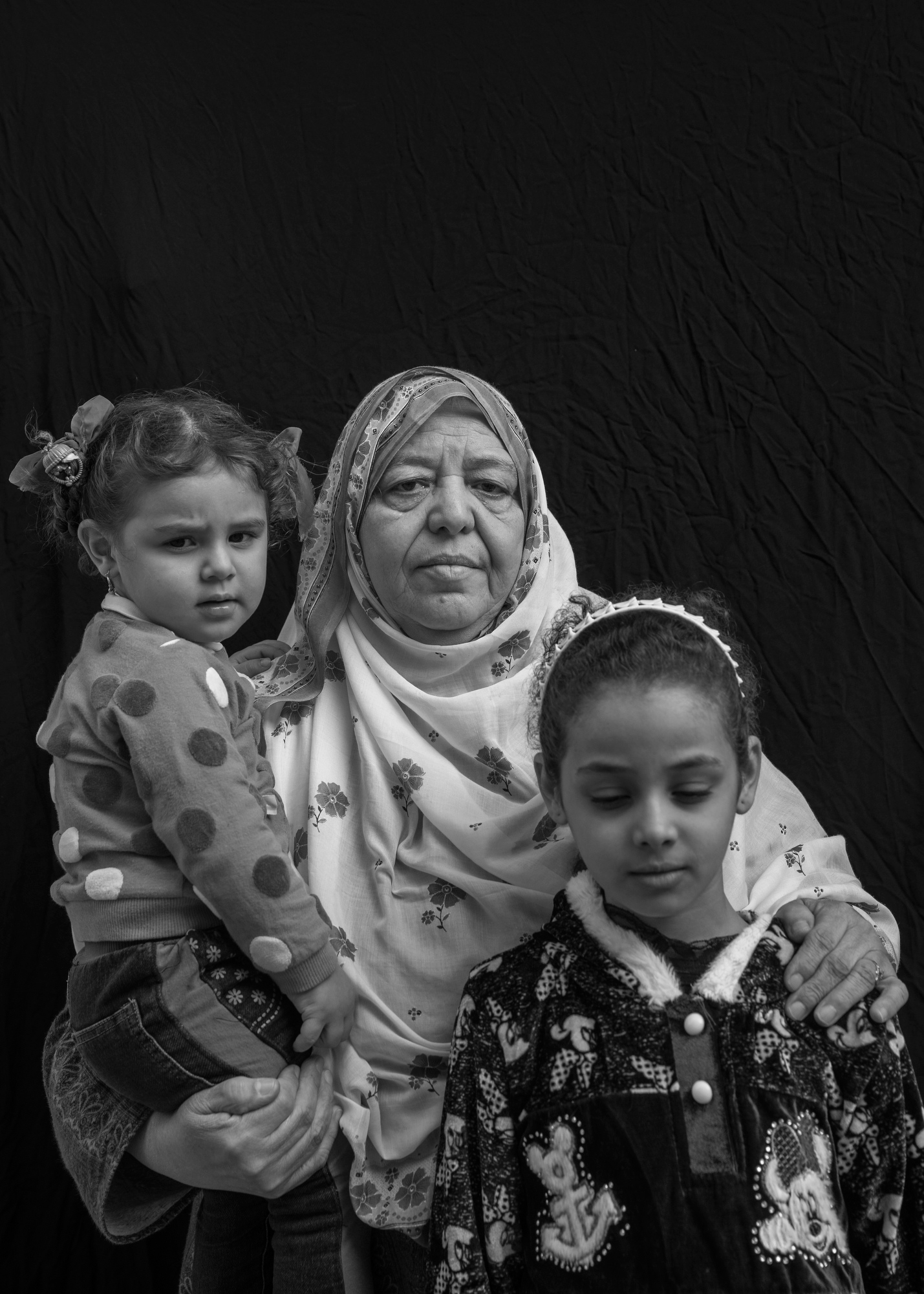 "Hawla Mahdi Salah, 67, poses for a portrait with her granddaughters Safae Khalid Adnan, 2, and Hawla Khalid Adnan, 9, in Mosul, Iraq. On June 26, 2017, an airstrike destroyed their home while they were inside. Salah lost nine family members in the blast, including two sons and three grandchildren, leaving her to care for Safae and Hawla who were orphaned, along with six other grandchildren. ""Only Allah knows if the Old City will be rebuilt,  she says."