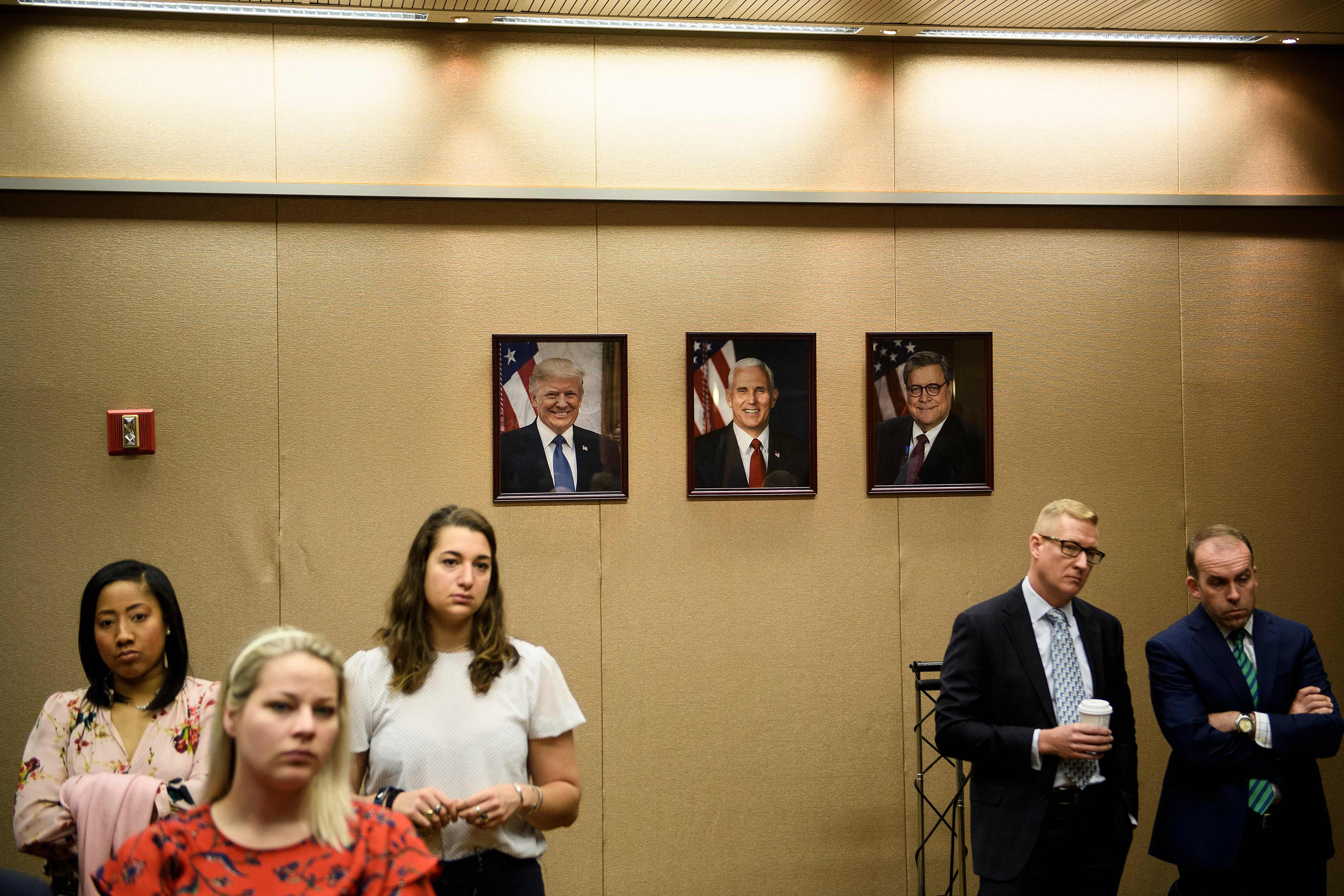 People listen while US Attorney General William Barr holds a press conference about the release of the Mueller Report at the Department of Justice April 18, 2019, in Washington, DC.