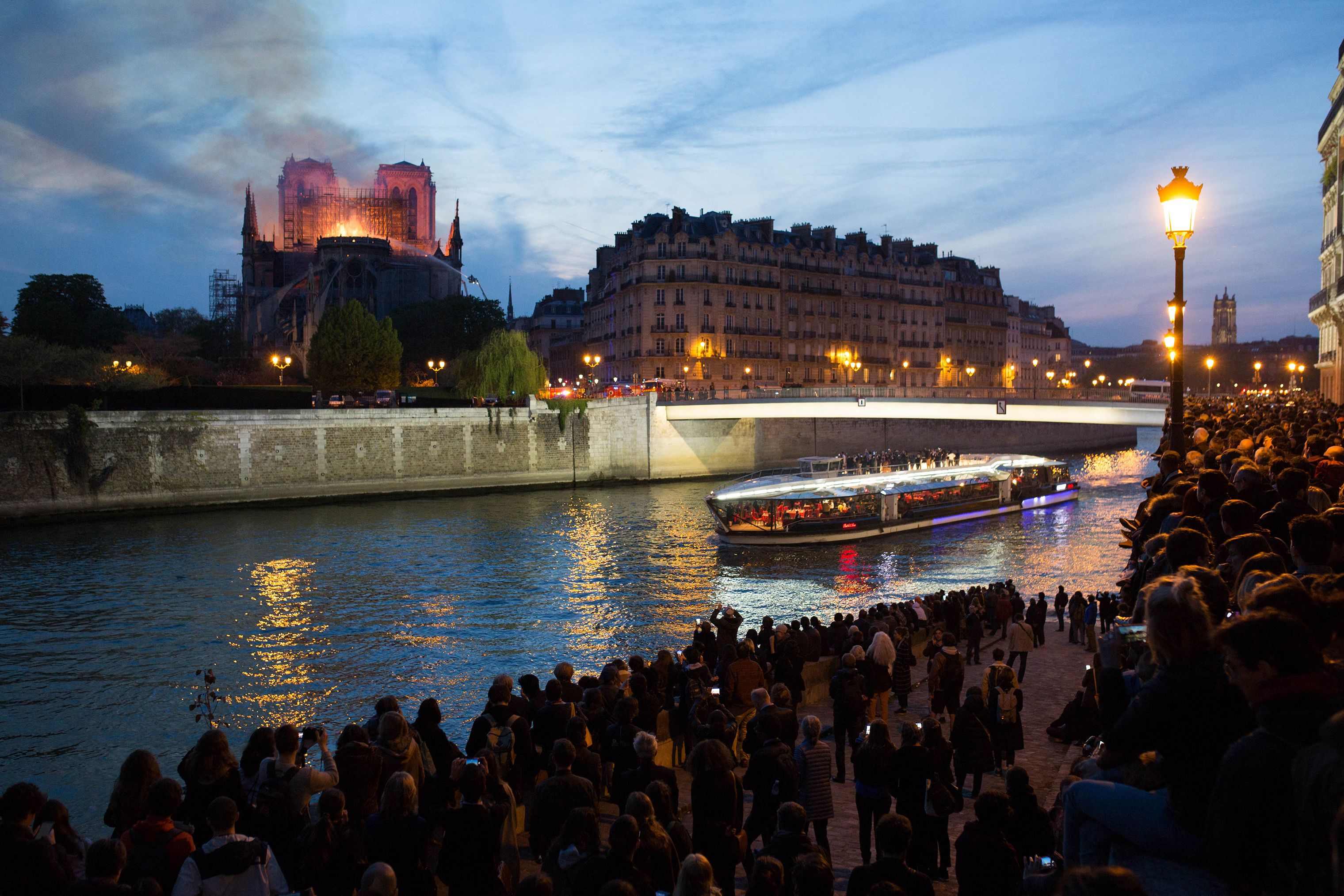 Bystanders look on as flames and smoke are seen billowing from the roof at Notre-Dame Cathedral with the Seine and boats by sun set river in Paris on April 15, 2019.