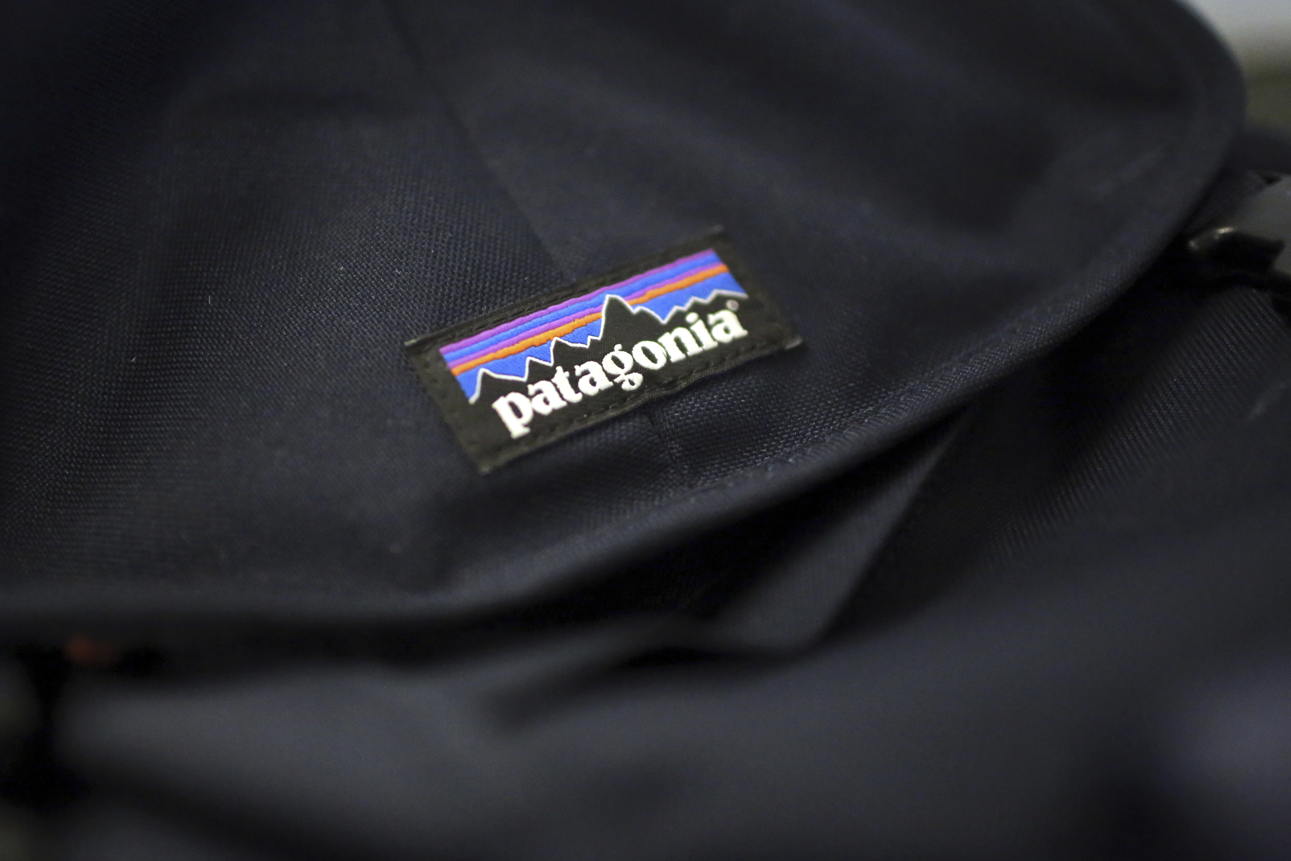 A Patagonia logo is sewn on a backpack Wednesday, Nov. 28, 2018, in New York. Patagonia Inc. is cracking down on the corporate logo vests when it comes to companies in financial sectors and other industries.