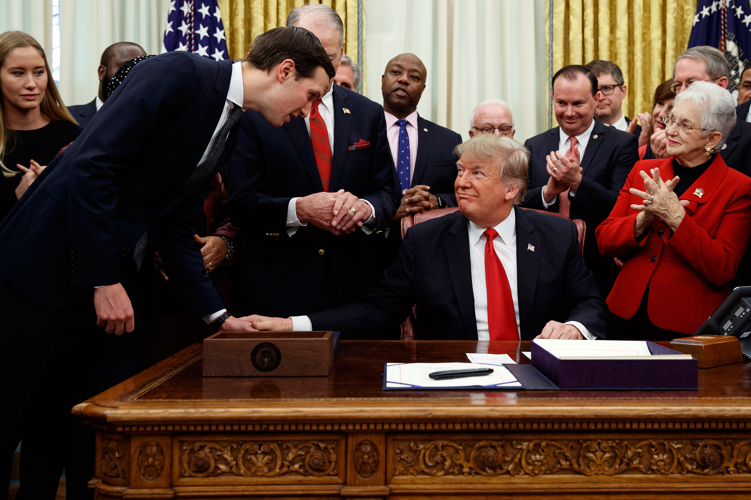 White House senior adviser Jared Kushner talks with President Donald Trump during a signing ceremony for criminal justice reform legislation in the Oval Office of the White House, Dec. 21, 2018.