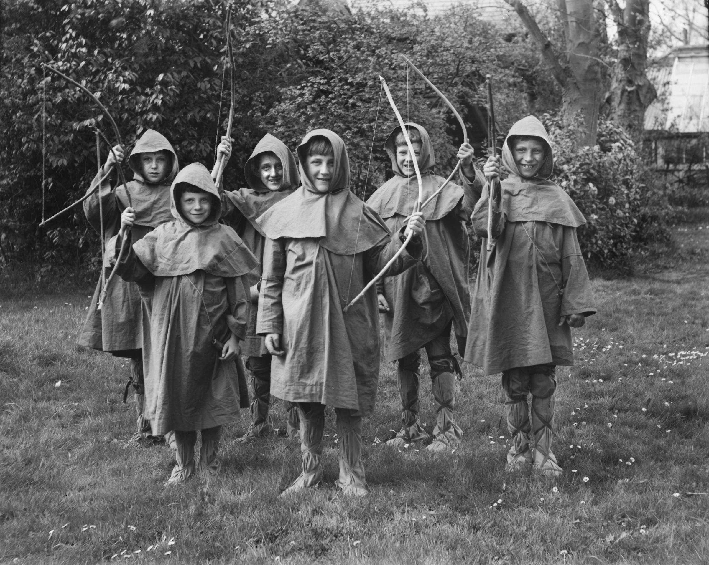 A group of school boys dressed as Robin Hood hold up their bows, U.K. ca. 1920.