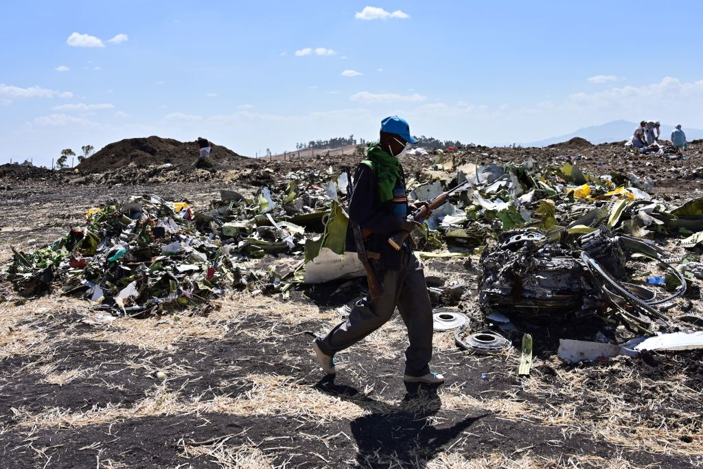 An Oromo man hired to assist forensic investigators walks by a pile of twisted airplane debris at the crash site of an Ethiopian airways operated Boeing 737 MAX aircraft on March 16, 2019 at Hama Quntushele village near Bishoftu in Oromia region. An American family has sued Boeing Co., Ethiopian Airlines and Rosemount Aerospace Inc. on April 3, 2019 on behalf of Samya Stumo who died in a plane crash.