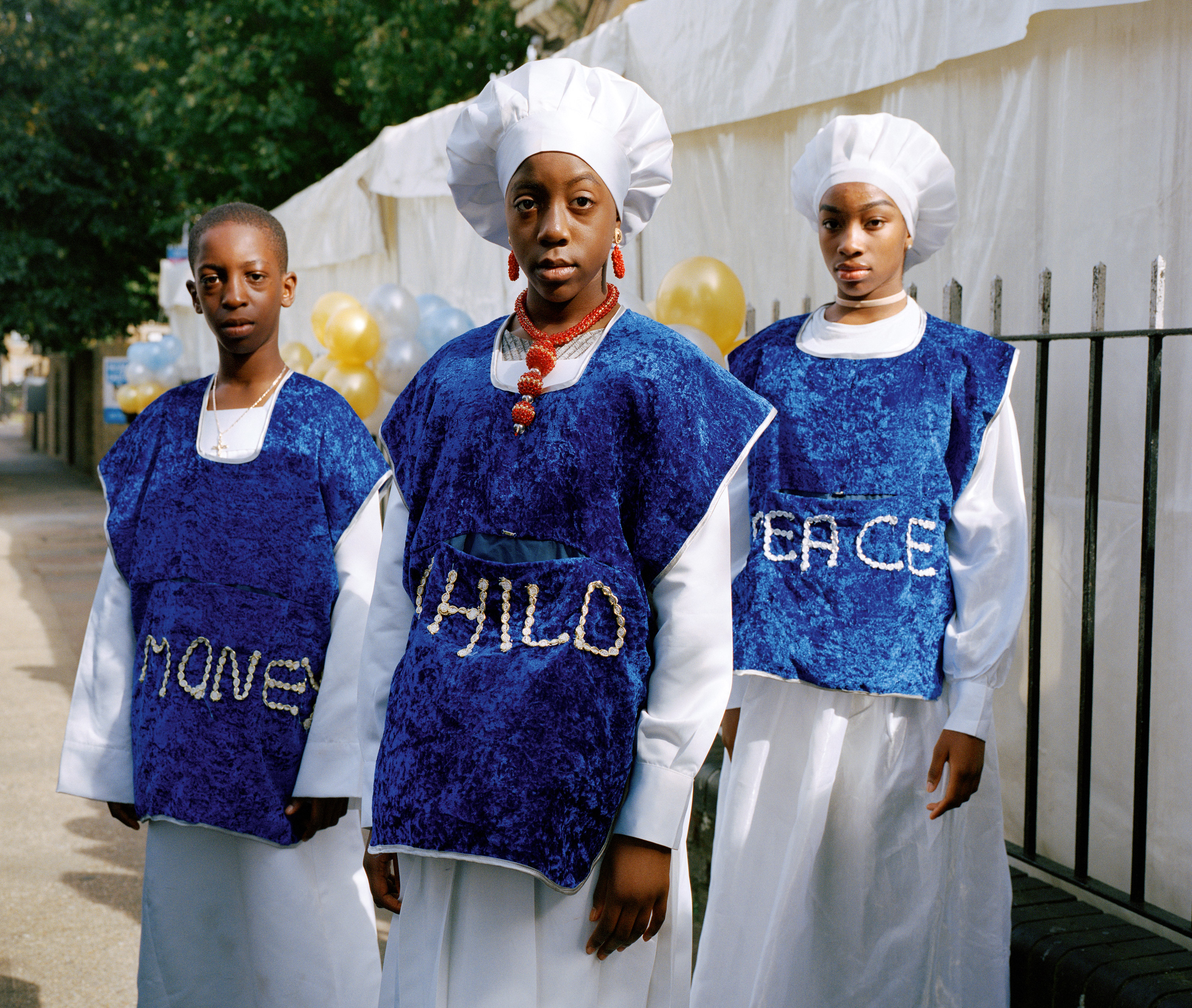 Josiah, Bukky and Lauren stand outside church on children's anniversary service wearing clothing that reads Money, Child, Peace as they collect donations from their fellow congregants for charity.