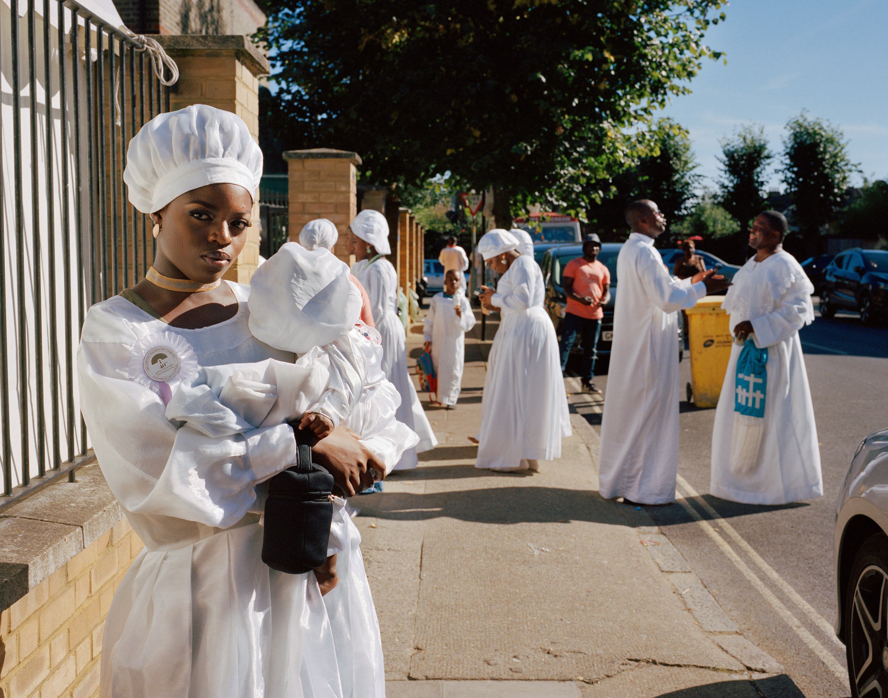 Hannah stands on the street holding her baby cousin whilst members of the Congregation greet each other and chat in the background of the street.