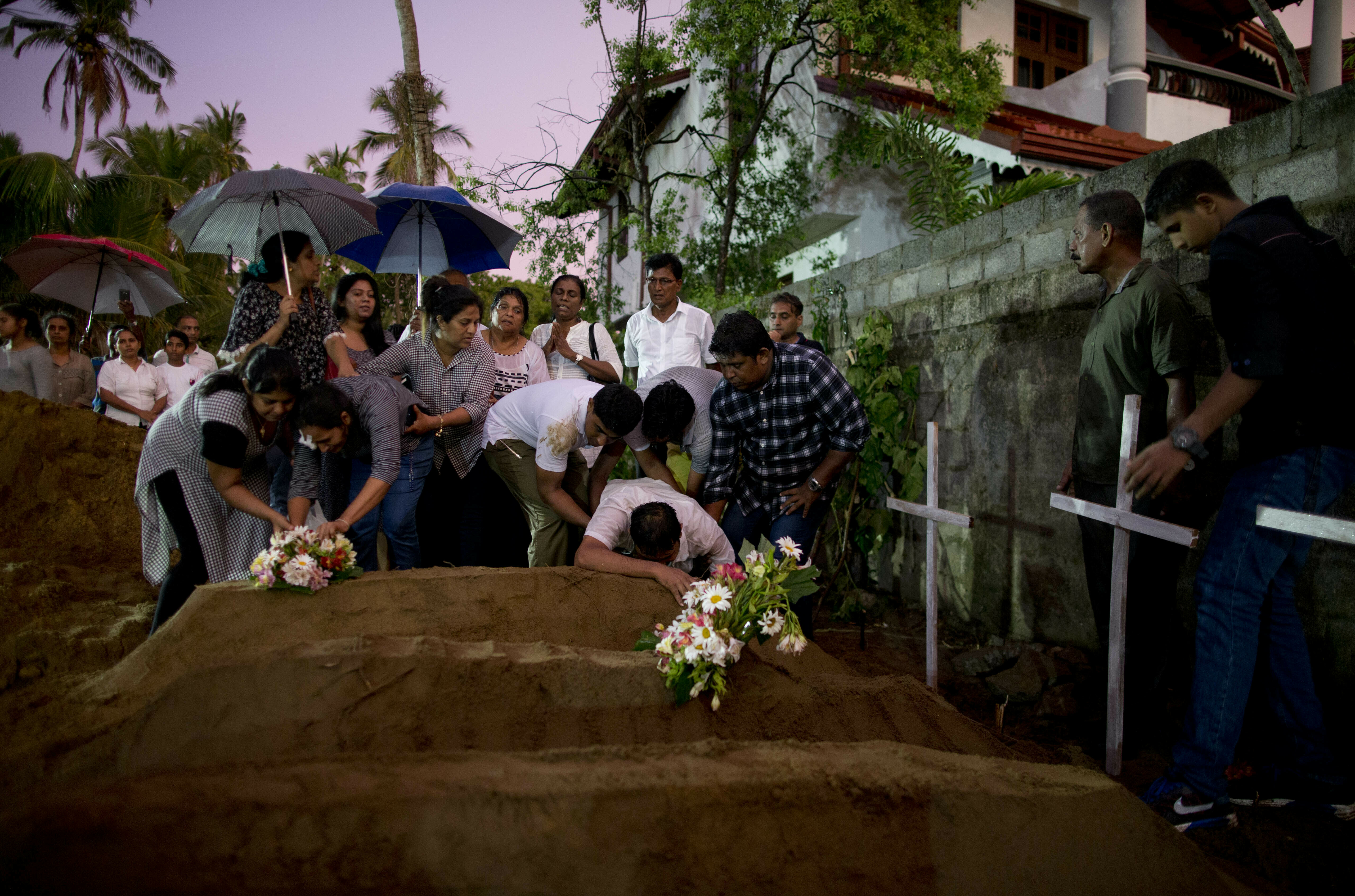 Relatives place flowers after the burial of three victims of the same family, who died at Easter Sunday bomb blast at St. Sebastian Church in Negombo, Sri Lanka, Monday, April 22, 2019. The State Department has confirmed that at least four Americans died in Sunday's attacks.