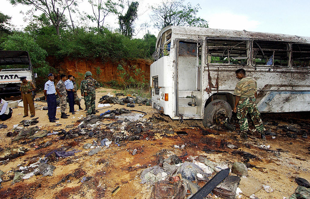 Sri Lanka security personnel look at the remains of a truck used by Tamil Tiger rebels to stage a suicide attack against bus loads of navy sailors in the north-eastern Sri lankan town of Habarana on Oct. 16, 2006.