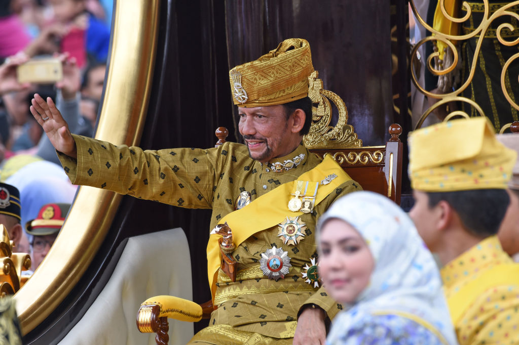 Brunei's Sultan Hassanal Bolkiah (L) waves from the royal chariot during a procession to mark his golden jubilee of accession to the throne in Bandar Seri Begawan on Oct. 5, 2017.