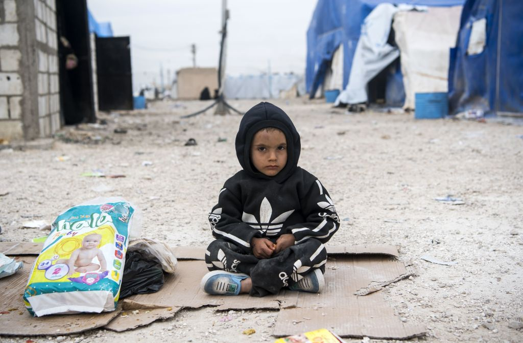 A displaced Syrian boy sits in front of tents and makeshift homes at a refugee camp in Al-Hol, northeastern Syria, on Feb. 6, 2019.