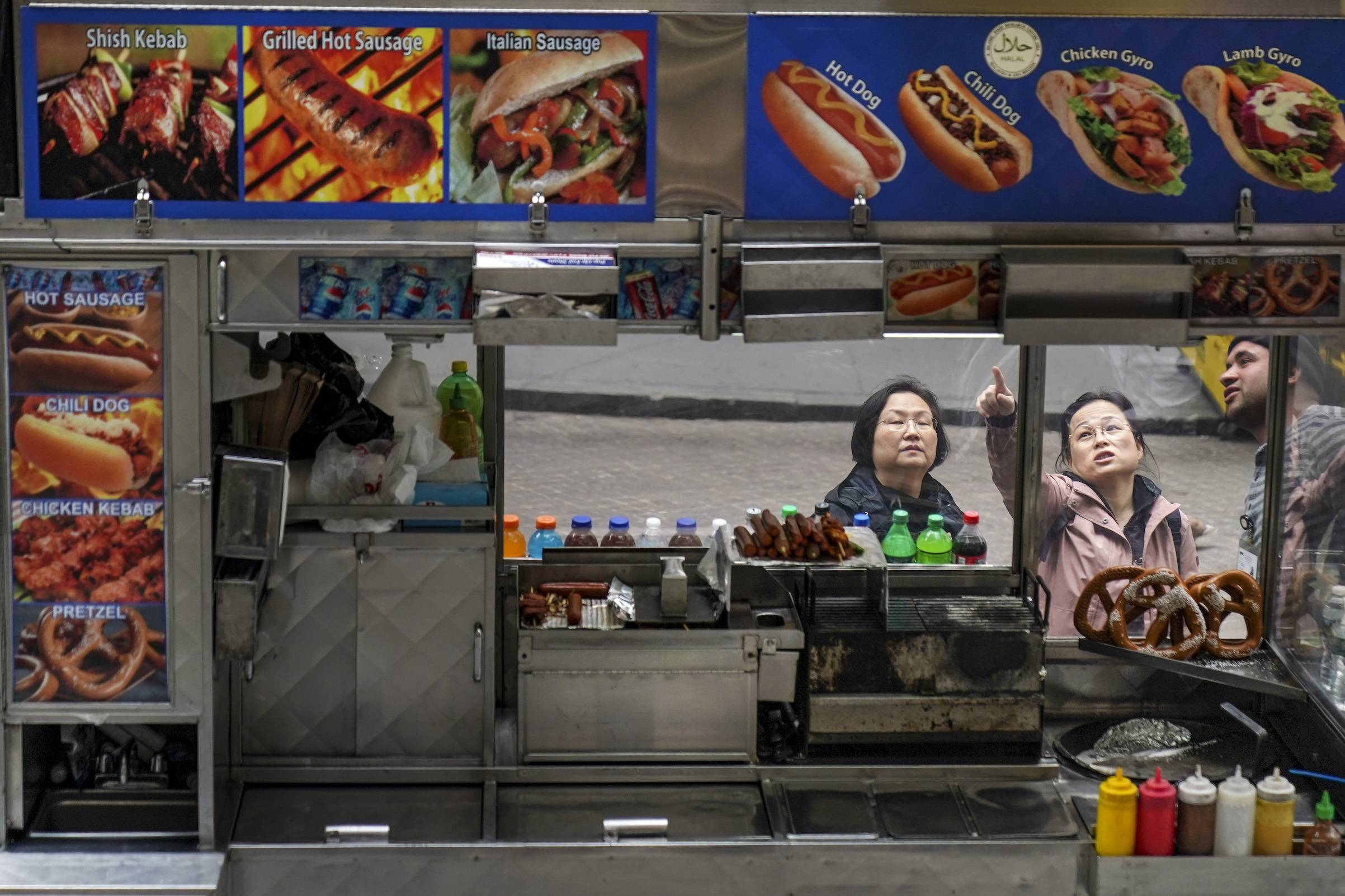 Customers order from a street food vendor on Wall Street during the lunch hour in Lower Manhattan, April 12, 2019 in New York City.