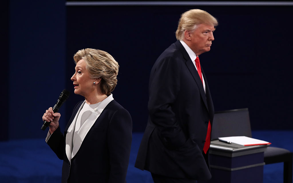 Democratic presidential nominee former Secretary of State Hillary Clinton speaks as Republican presidential nominee Donald Trump listens during the town hall debate at Washington University on Oct. 9, 2016 in St Louis, Missouri.