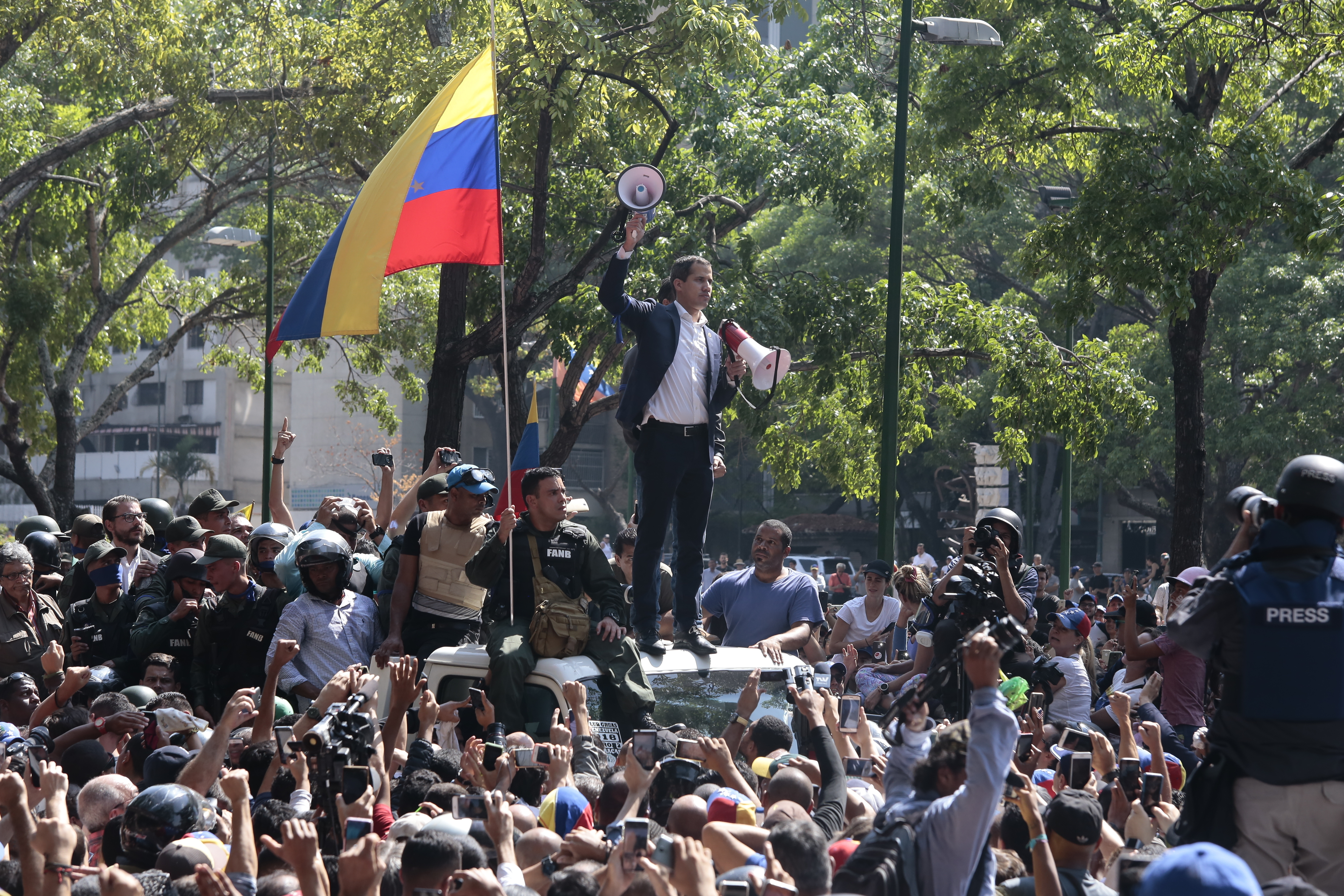 Juan Guaido, self-proclaimed interim president of Venezuela, stands with two megaphones in his hands surrounded by soldiers and civilians at Plaza Altamira on April 30, 2019 in Caracas, Venezuela.  As interim president of Venezuela, as legitimate supreme commander of the armed forces, I call on all soldiers to join us,  says the opposition leader on a highway.