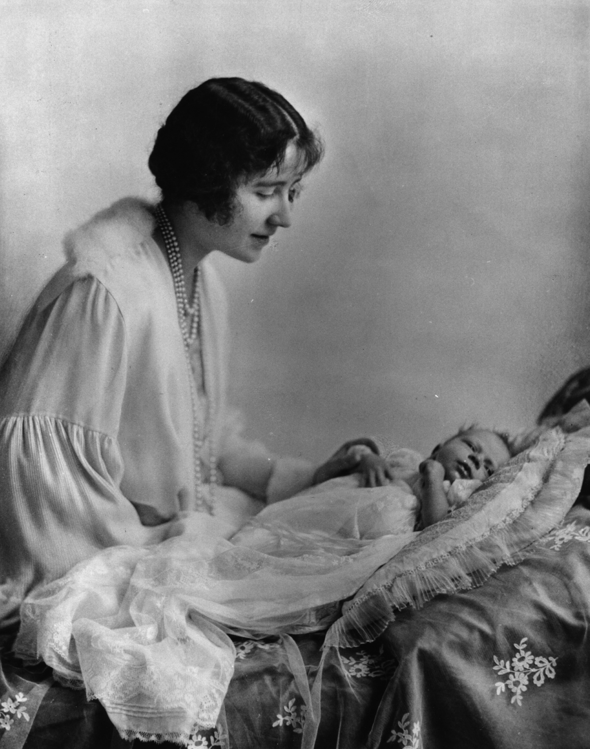 May 1926: Elizabeth, Duchess of York (1900 - 2002), looking at her first child, future Queen, Princess Elizabeth.
