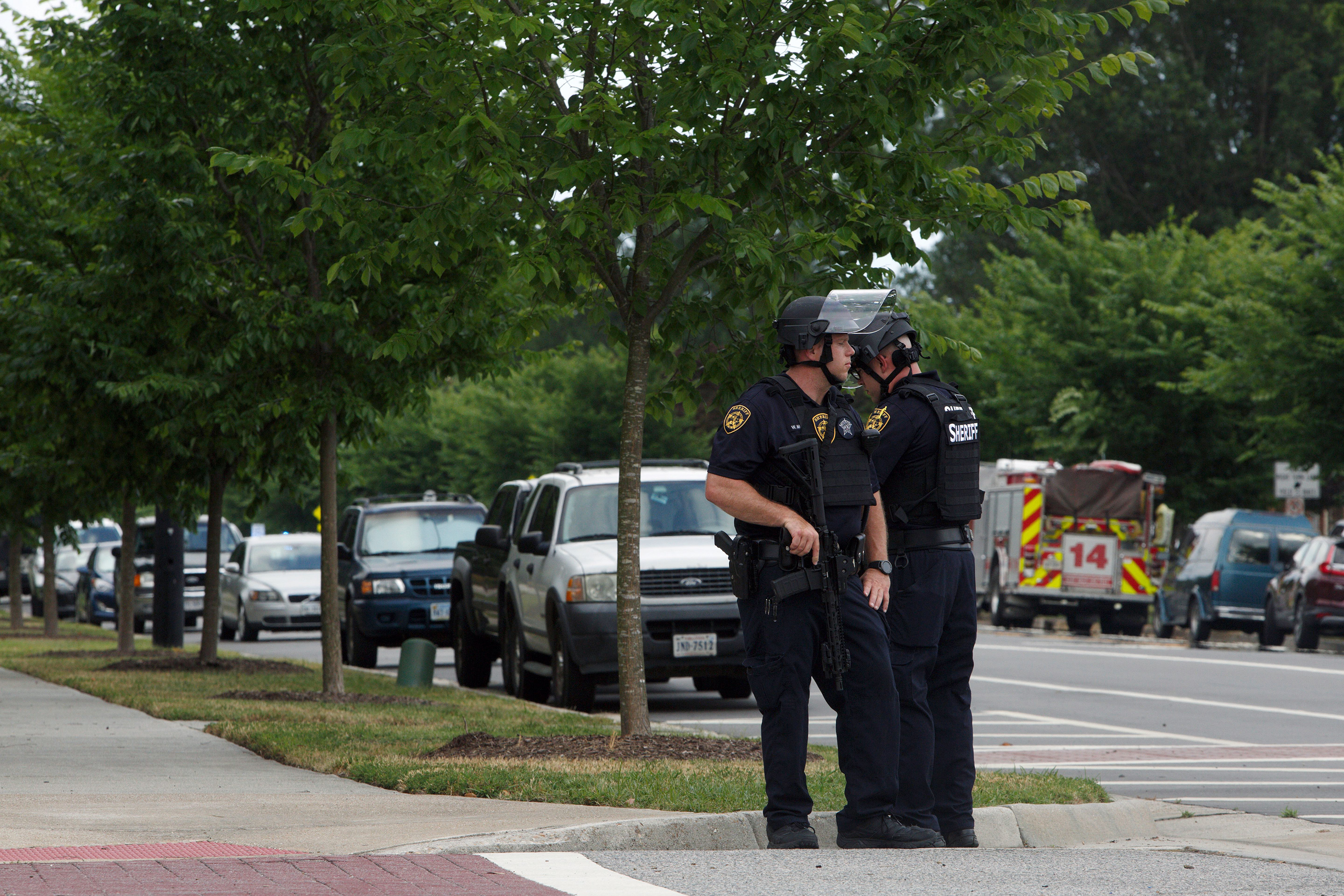 Virginia Beach police officers huddle near the intersection of Princess Anne Road and Nimmo Parkway following a shooting at the Virginia Beach Municipal Center on May 31, 2019.