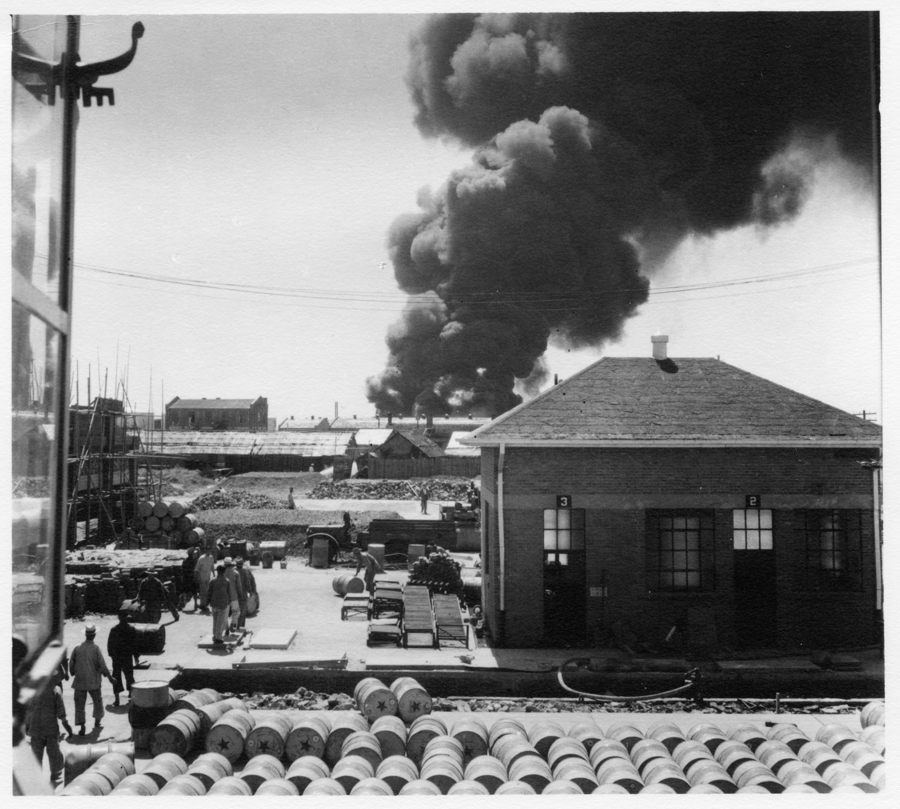 Smoke rises from the neighboring Standard Vacuum Oil Terminal where the heaviest fighting took place.