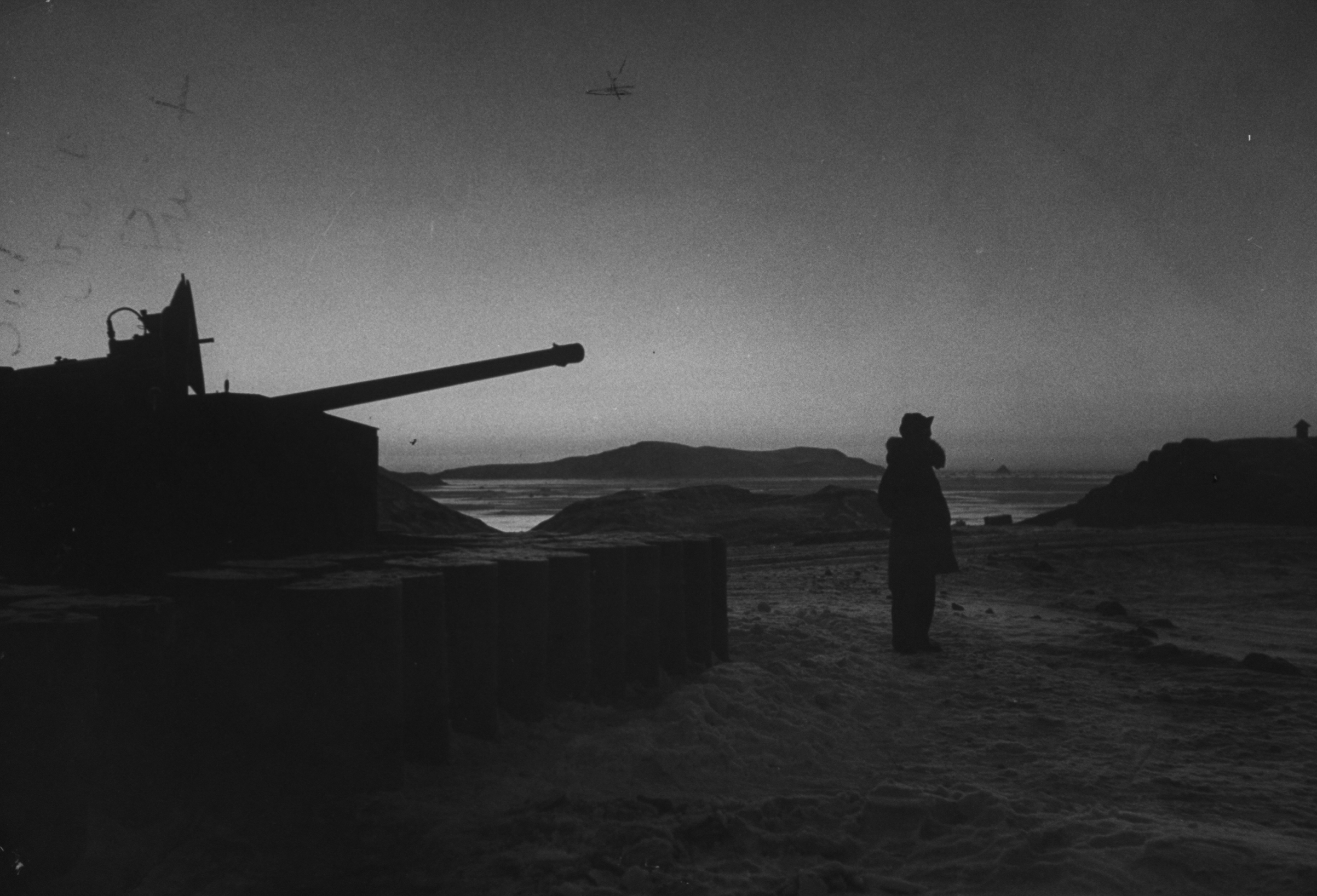 Antiaircraft gun such as this one guarded by an artilleryman in 1953 formed part of Thule Air base's intensive armament system and were manned on a 24-hour basis