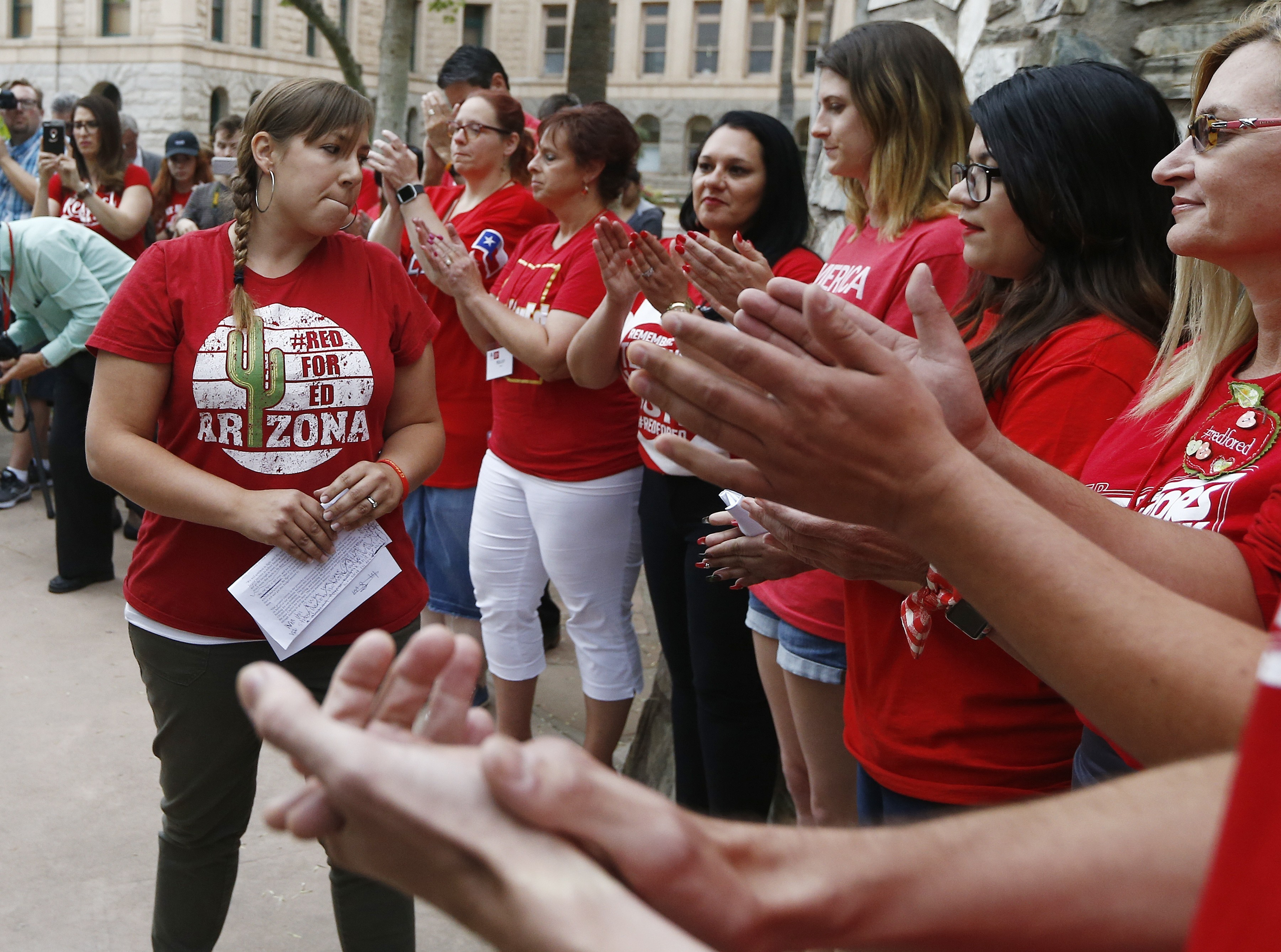 Phoenix teacher Rebecca Garelli, left, an Arizona Educators United member, is applauded after her announcement from protest organizers that teachers intend to go back to work as the statewide teachers strike enters a fourth day at the Arizona Capitol on May 1, 2018, in Phoenix.