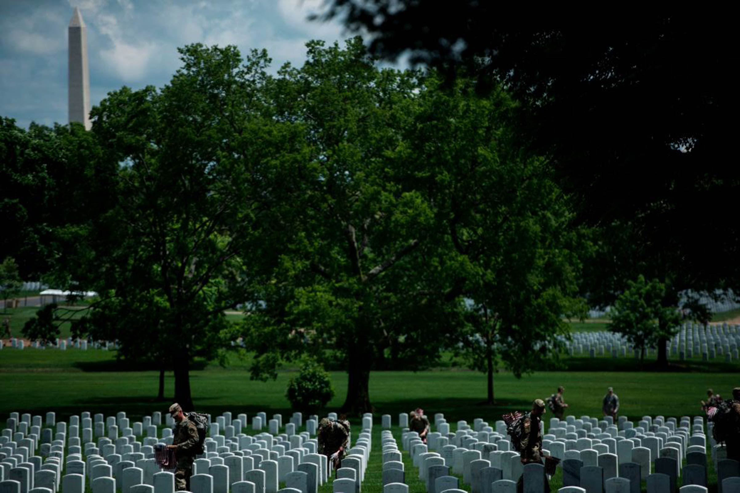 Soldiers in the Old Guard place flags at graves in Arlington National Cemetery during  Flags In  in preparation for Memorial Day May 25, 2017, in Arlington, Virginia.