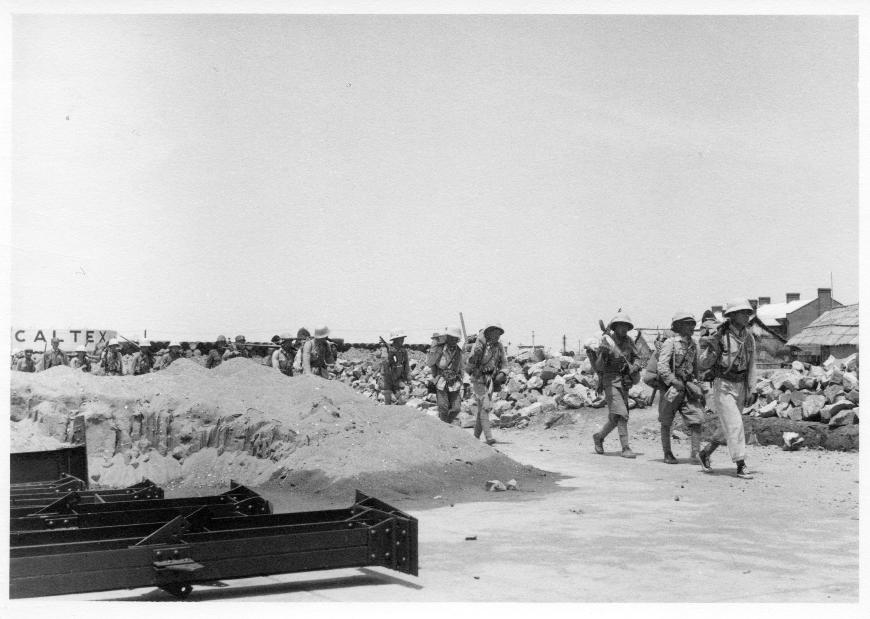 Nationalist troops march through the Caltex property to the battlefront. A Caltex oil tank is visible in the background.