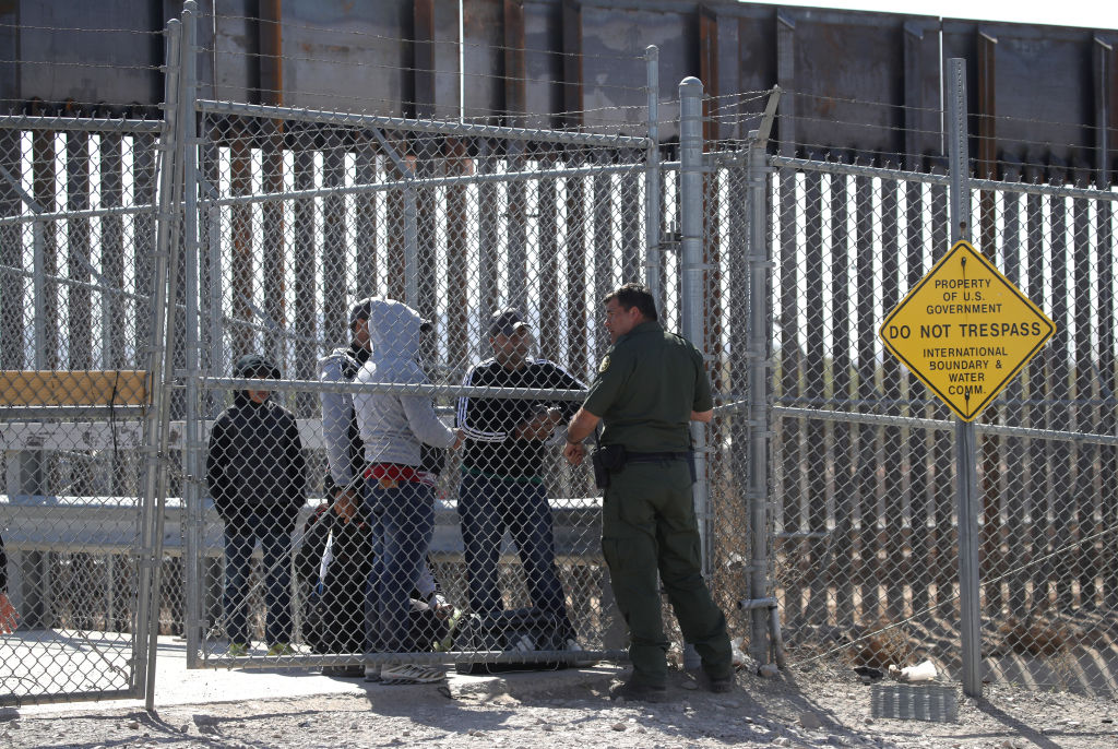 A patrol agent talks with detained migrants at the U.S.-Mexico border in El Paso, Texas, on March 31, 2019.