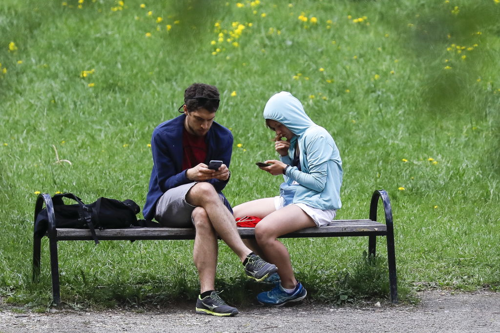 Young people sitting on a bench at the VDNKh exhibition centre and park, in Moscow, on May 11, 2019.