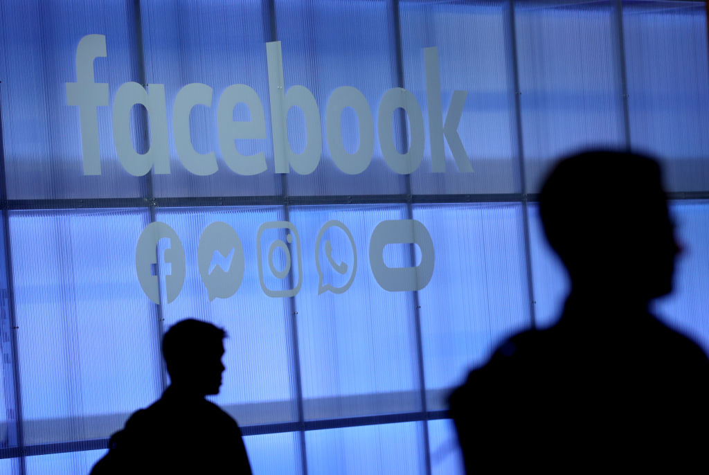 The Facebook logo is displayed during the F8 Facebook Developers conference on April 30, 2019 in San Jose, California. Facebook is banning Alex Jones, Milo Yiannopoulos and others for violating their policies on hate speech.