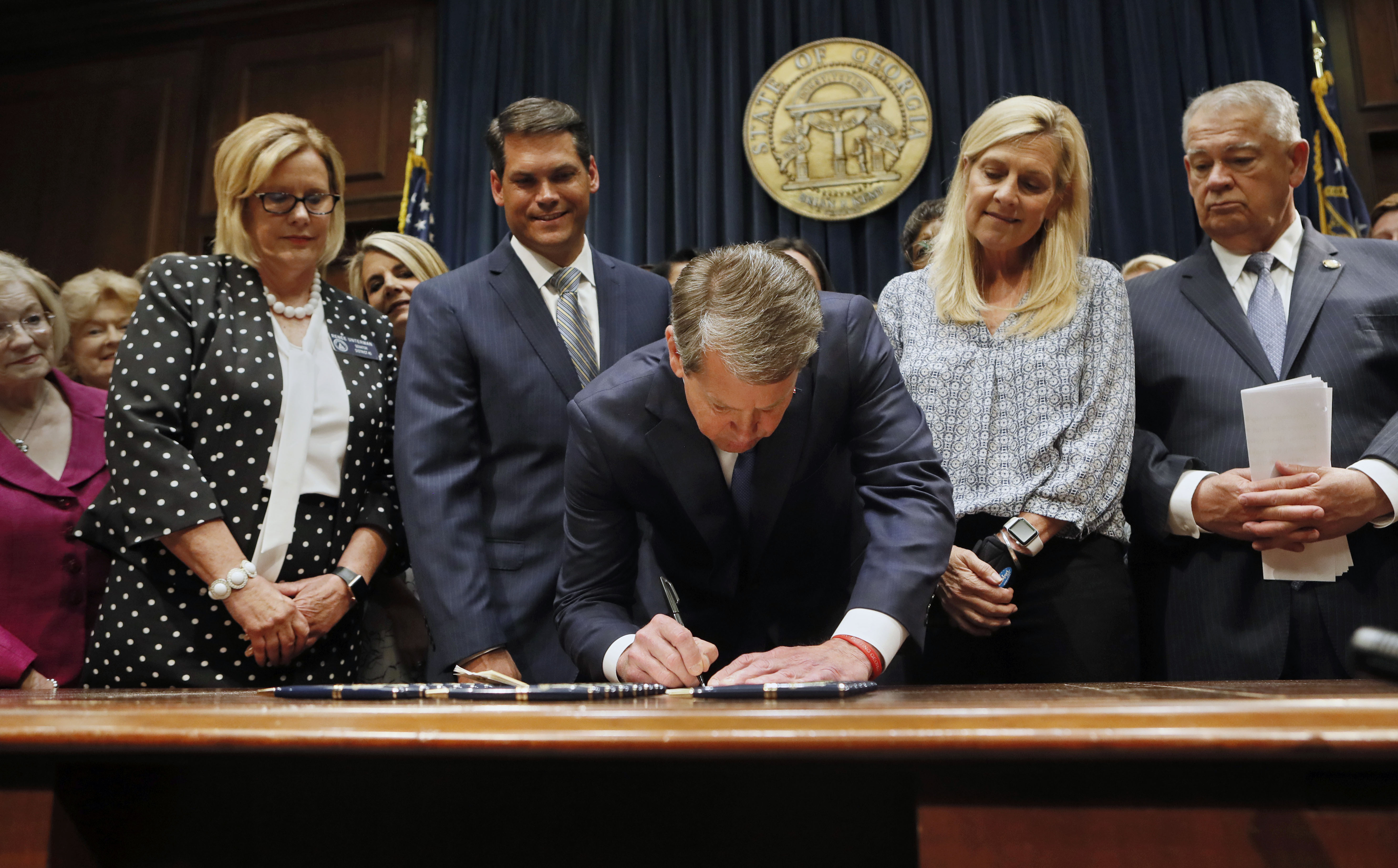 Surrounded by supporters of the bill, including Sen. Renee Unterman (from left), R  -Buford, Lt. Gov. Geoff Duncan, First Lady Marty Kemp, and House Speaker David Ralston, Gov. Brian Kemp signed HB 481, the  heartbeat bill , on Tuesday, May 7, 2019 in Atlanta, setting the stage for a legal battle as the state attempts to outlaw most abortions after about six weeks of pregnancy.