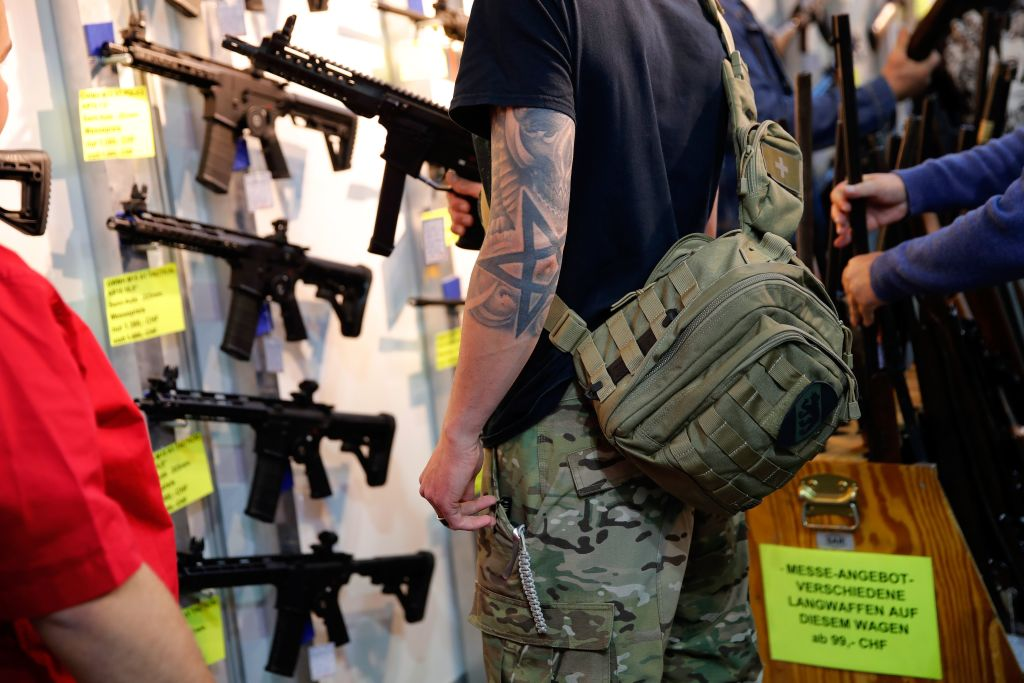 A visitor holds a semi-automatic shotgun during the 45th edition of the Arms Trade Fair, in Lucerne, Switzerland on March 29, 2019