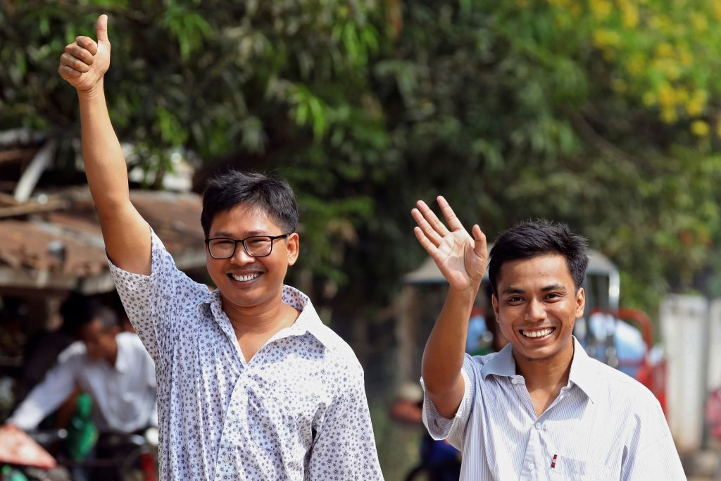 Reuters journalists Wa Lone (L) and Kyaw Soe Oo gesture as they walk to Insein prison gate after being freed in a presidential amnesty in Yangon on May 7, 2019