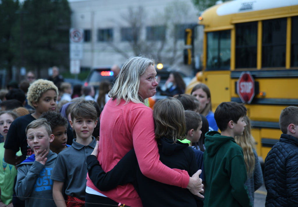 Students escorted on school bus in front of STEM School Highlands Ranch after a shooting. May 7, 2019.