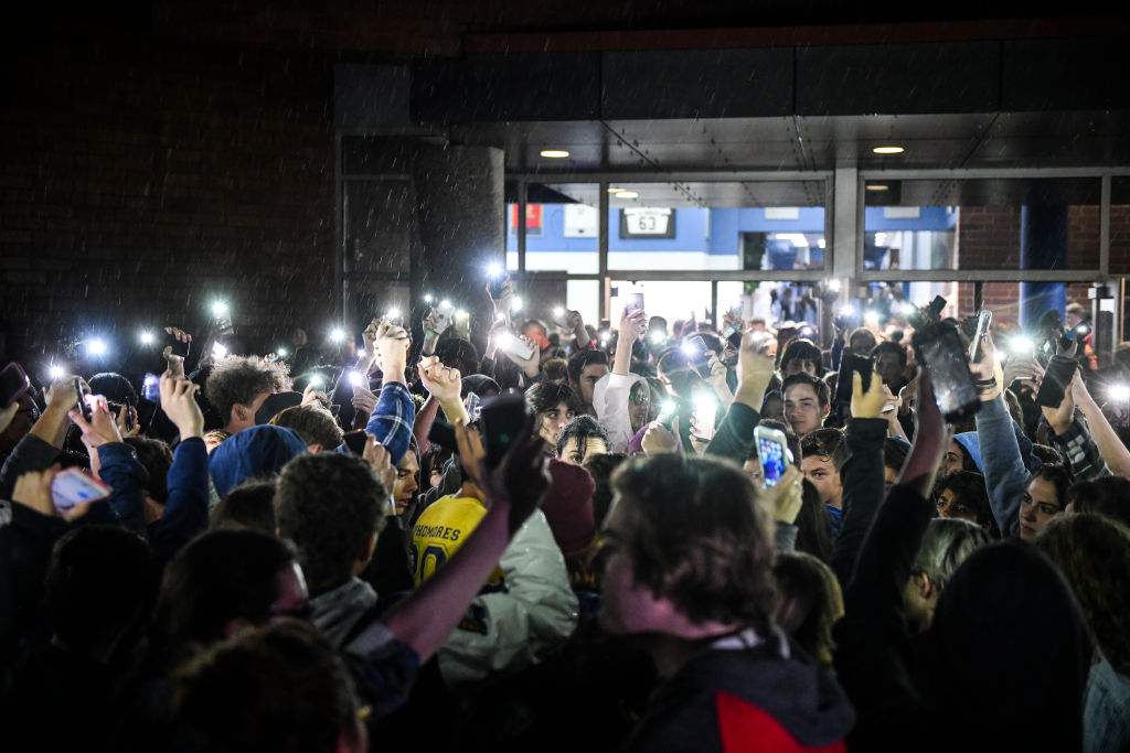 Students hold up their phones after leaving a candlelight vigil at Highlands Ranch High School on May 8, 2019.