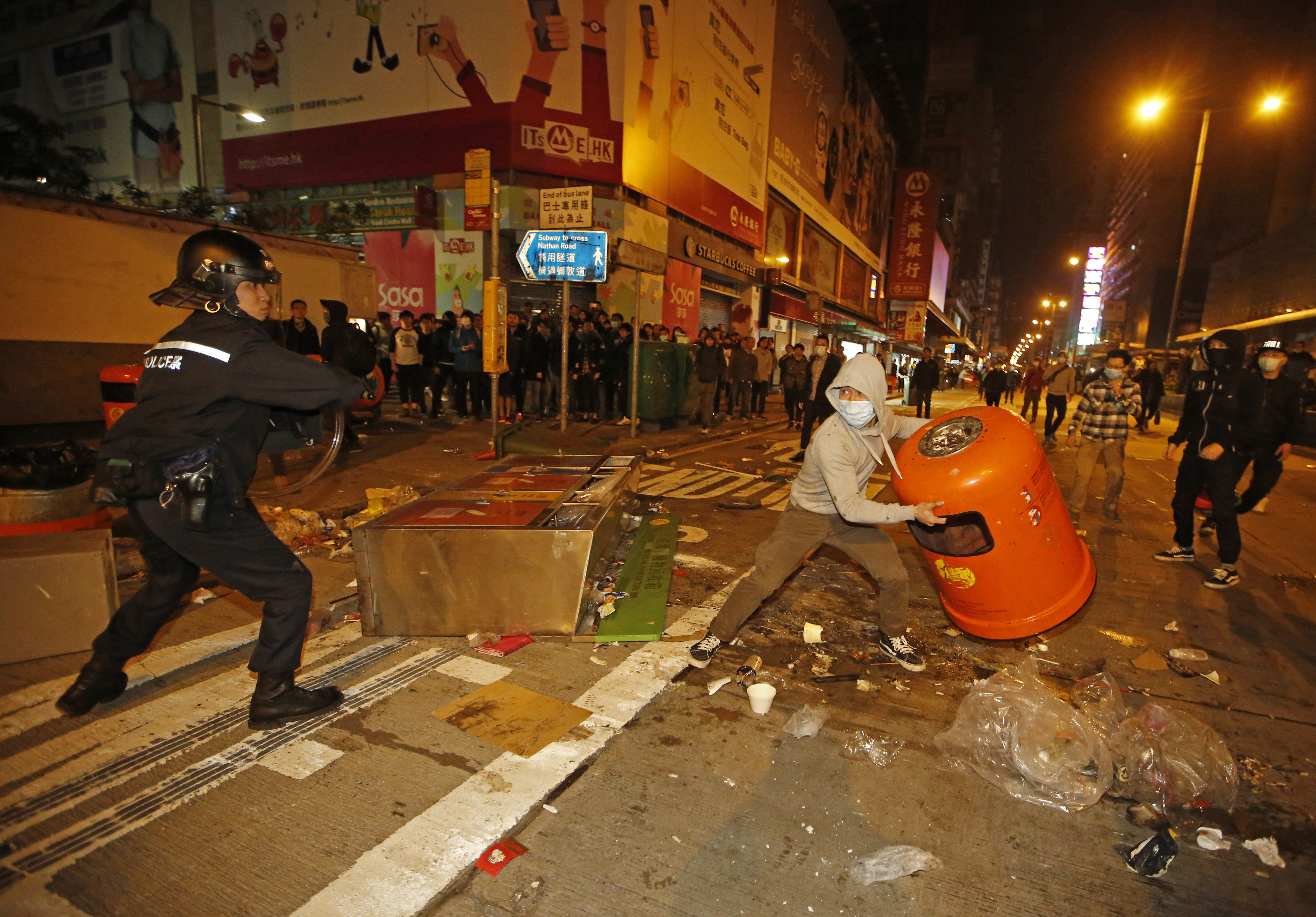 A rioter tries to throw a litter bin at police on a street in Mongkok district of Hong Kong, Feb. 9, 2016.