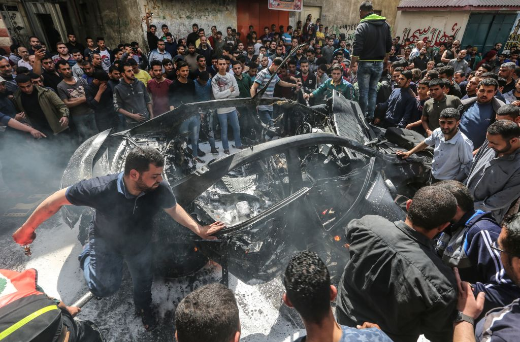 Palestinian emergency personnel try to put out the fire on a car belonging to Hamas member Hamad al-Khodori, in Gaza City on May 5, 2019, after it was hit by an Israeli airstrike. A Palestinian militant was killed in an Israeli retaliatory strike in the Gaza Strip, Gazan officials said, in response to rocket barrages fired from the enclave.