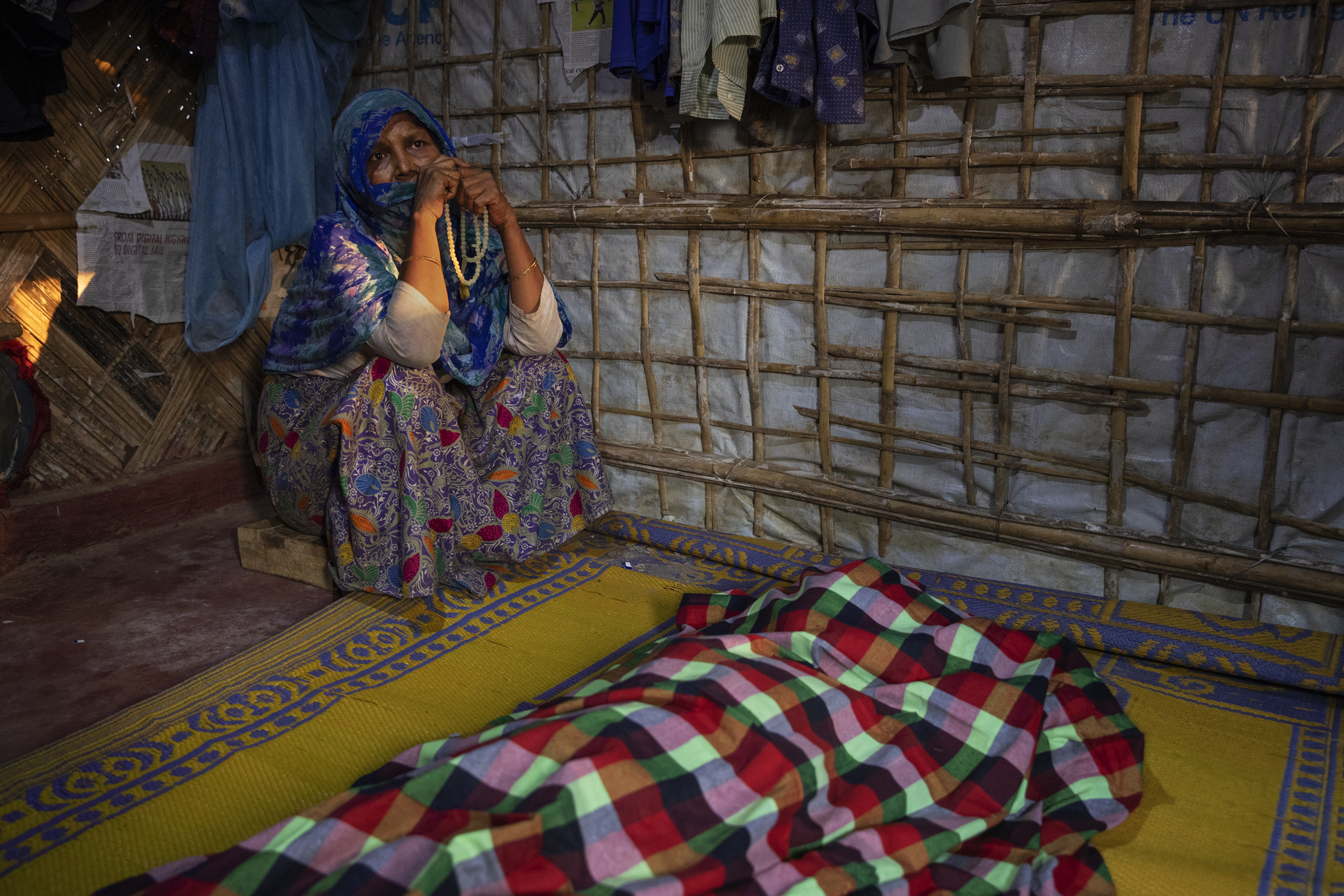 A woman grieves for Fatema Begum, 60, in the hut of the deceased.