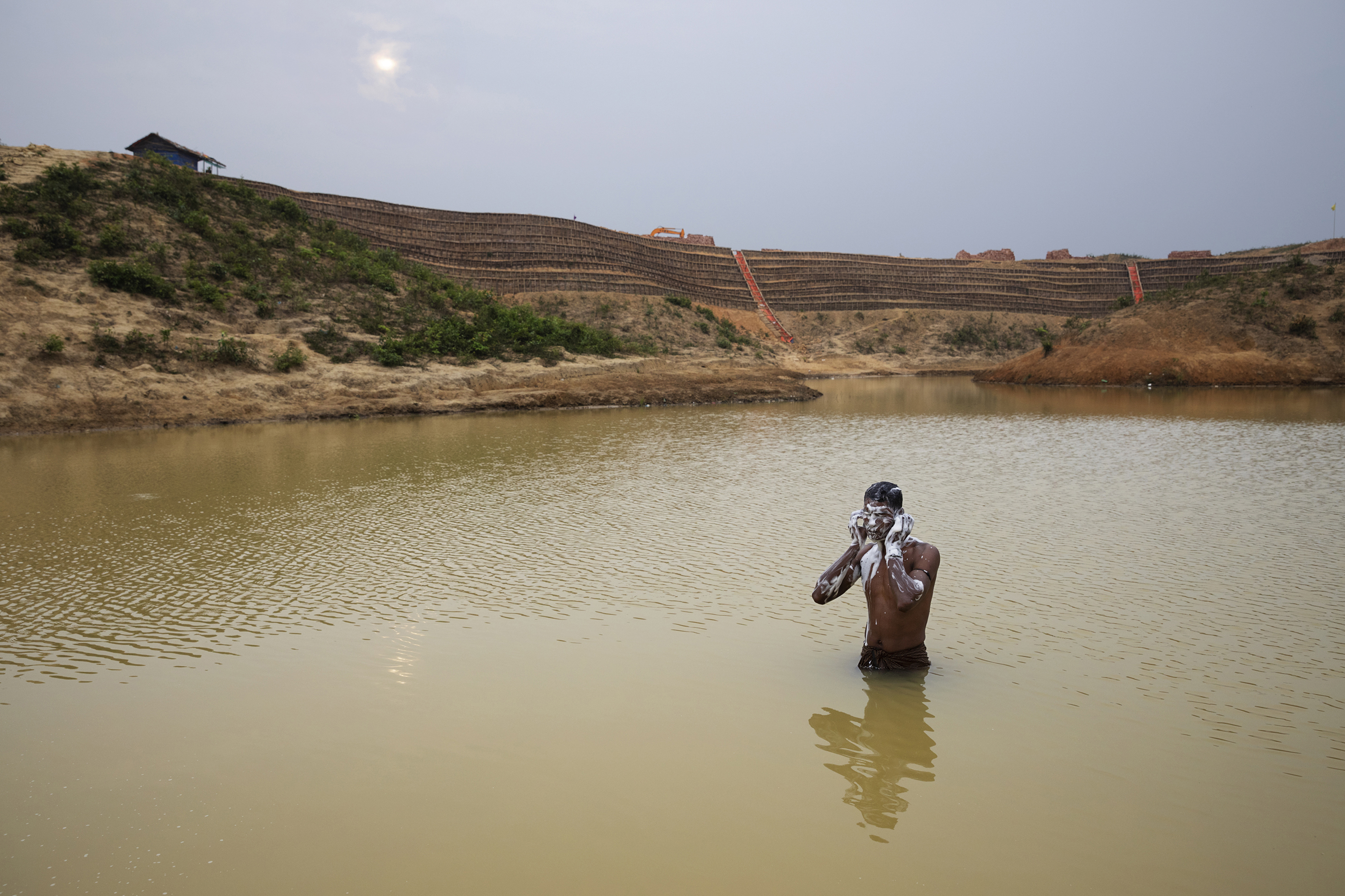 A man bathes in a man-made pond near the camp where he lives. Behind him is the construction of the Camp 20 Extension.