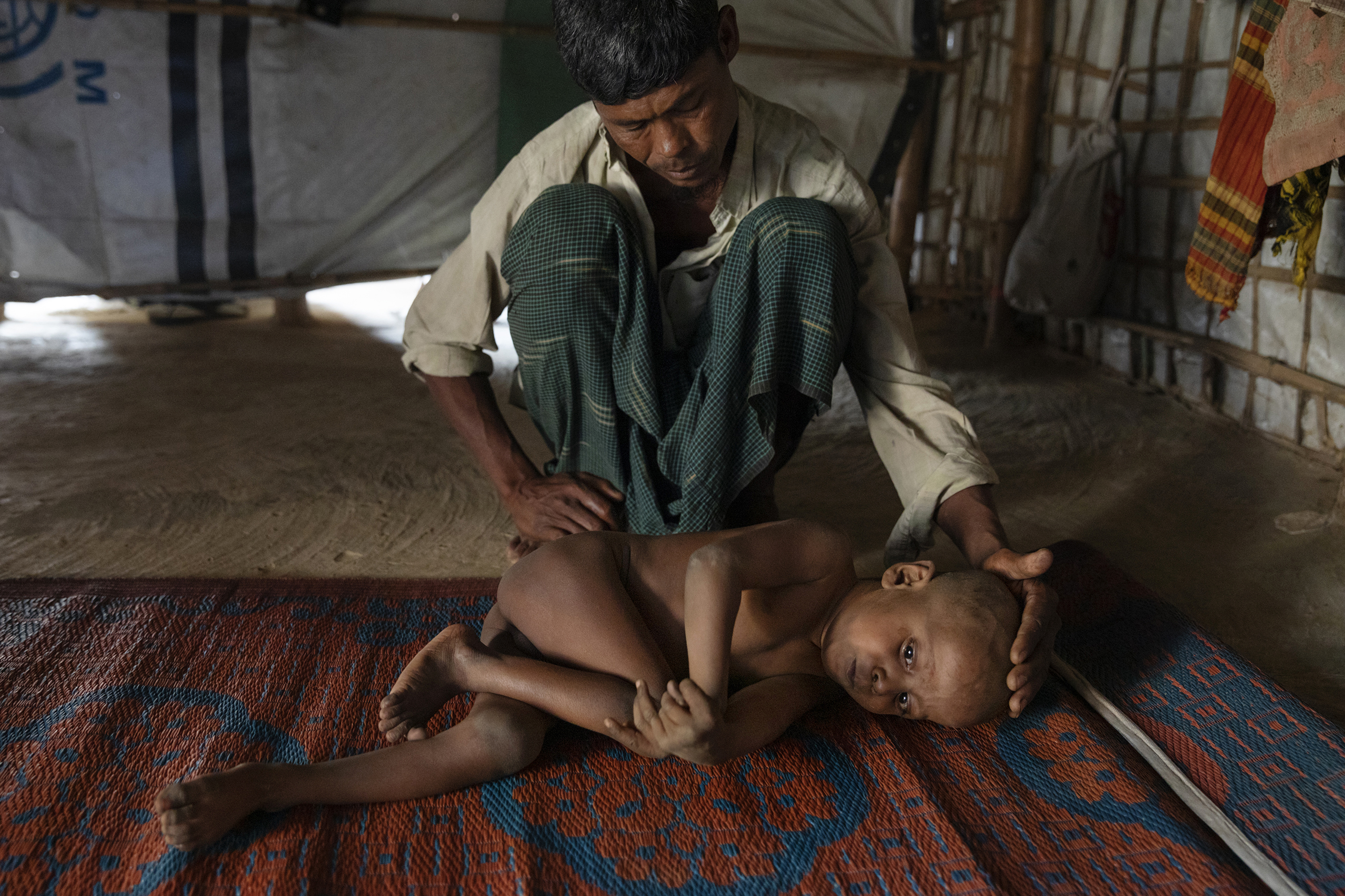 Mohammed Amin cares for his sick son, 7-year-old Mujibur Rahman, in a hut. The boy suffers from a nervous system disorder, his father said.
