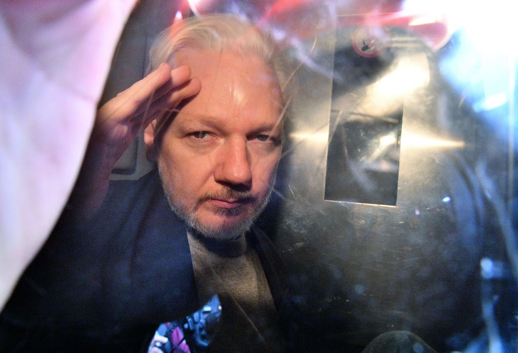 WikiLeaks founder Julian Assange gestures from the window of a prison van as he is driven out of Southwark Crown Court in London on May 1, 2019.