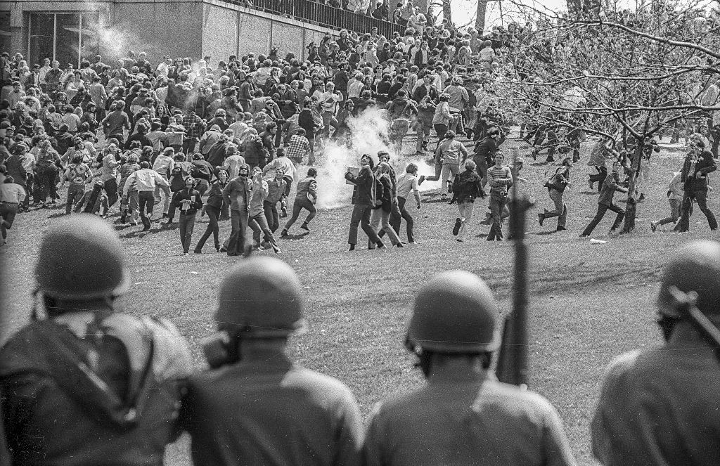 View, from behind, as Ohio National Guardsmen in gas masks and with rifles as they prepare to advance up Blanket Hill, through clouds of teargas, to drive back Kent State University students during an antiwar demonstration on the university's campus, Kent, Ohio, May 4, 1970. Visible at left is Taylor Hill. The protests, initially over the US invasion of Cambodia, resulted in the deaths of four students (and the injuries of nine others) after the National Guard opened fire on students.