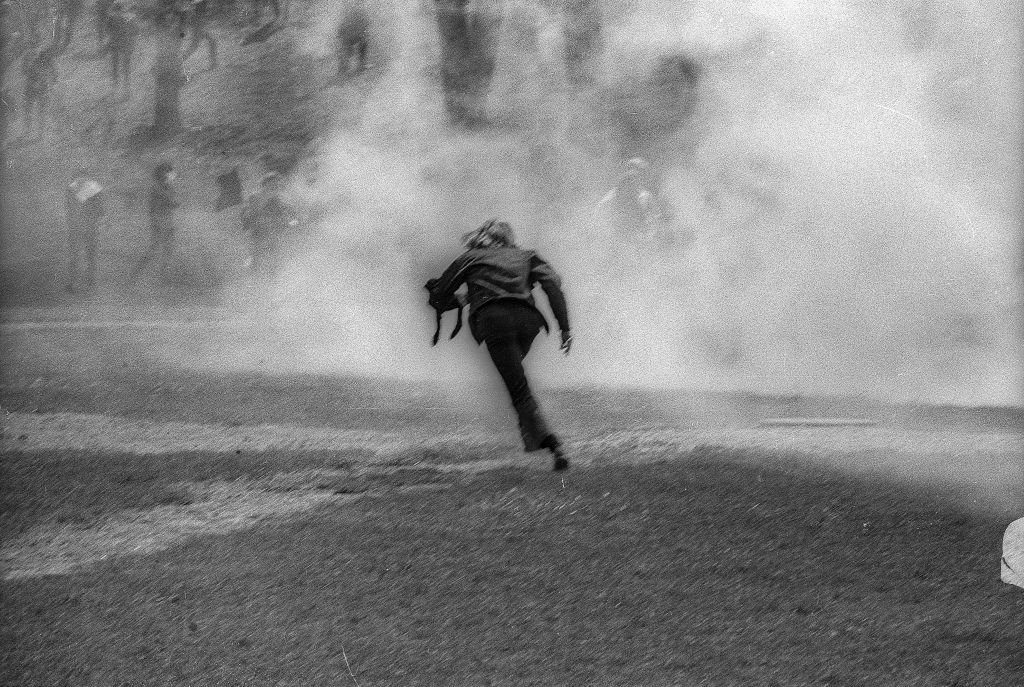 An unidentified demonstrator runs through a cloud of teargas on the Kent State University Commons during a student antiwar protest, Kent, Ohio, May 4, 1970. The protests, initially over the US invasion of Cambodia, resulted in the deaths of four students (and the injuries of nine others) after the National Guard opened fire on students.