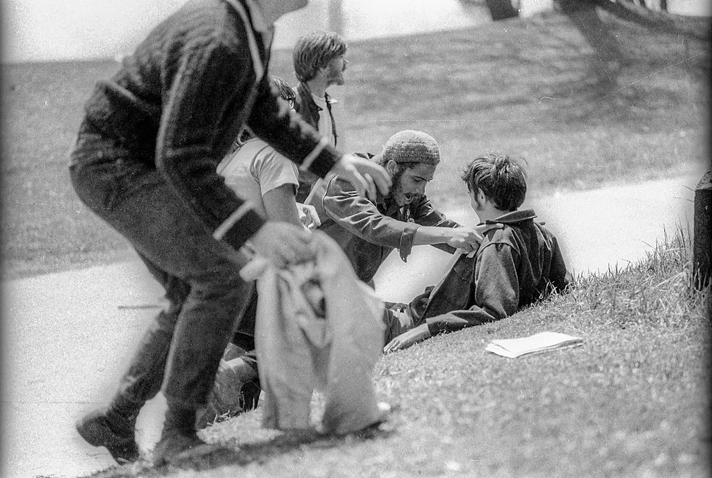 Students kneel on the grass beside wounded classmate John Cleary after the latter had been shot when the Ohio National Guard opened fire on antiwar protesters, Kent, Ohio, May 4, 1970.
