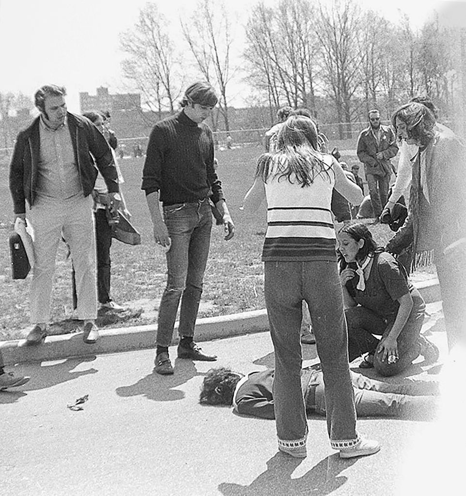 Teenager Mary Ann Vecchio (kneeling, with white neckerchief) and others surround the body of Kent State University student Jeffrey Miller (1950 - 1970) who had been shot during an anti-war demonstration on the university campus, Kent, Ohio, May 4, 1970. The protests, initially over the US invasion of Cambodia, resulted in the deaths of four students, including Miller, and the injuries of nine others after the National Guard opened fire on students. Vecchio (who was not a KSU student) was also photographed in the Pulitzer prize-winning photograph (also by John Filo) that came to define the event.