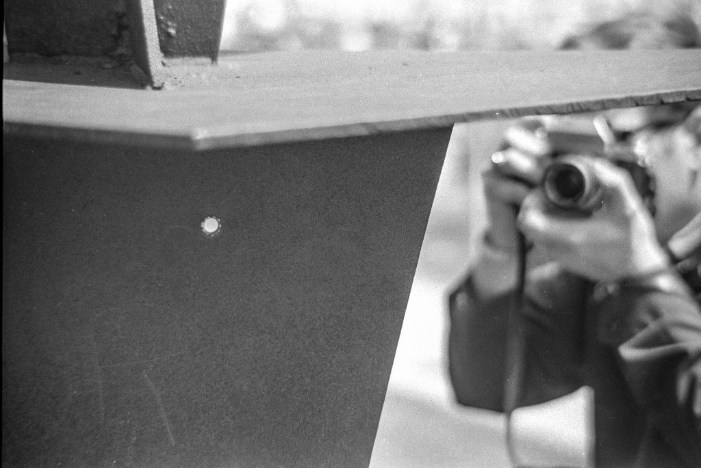 Closeup of a bullet hole left in a metal sculpture after the Ohio National Guard opened fire on antiwar protesters at Kent State University, Kent, Ohio, May 4, 1970. In the background, an unidentified person photographs the hole from the opposite side. The sculpture, 'Solar Totem #1' by Don Drumm, is located outside Taylor Hall.