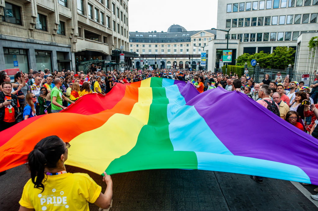 People are seen holding a big rainbow flag during the 24th Belgian Pride parade in Brussels on May 18, 2019.